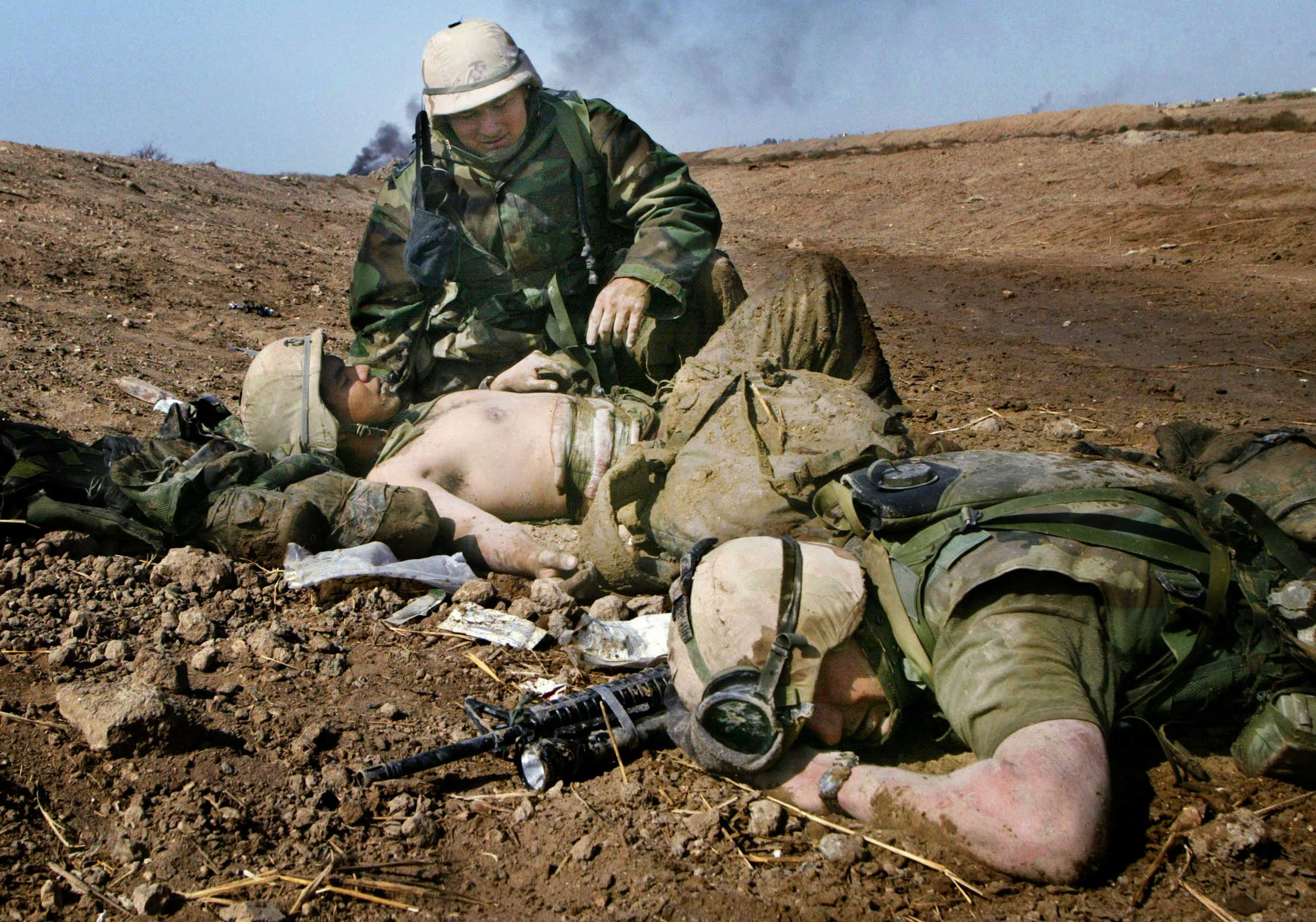 <b>Joe Raedle, March 23, 2003                                   </b>                                   Ten years ago, I was in the desert of southern Iraq, documenting the lives of U.S. Marines from Task Force Tarawa 1/2 Charlie Company as they fought in the town of Nasiriyah at the start of the war.                                    It was the first major battle these young Marines had encountered. They lost 18 fellow Marines and 14 more were wounded in the bloody fight. I saw these kids become men in a matter of hours. All the bravado, adrenaline and laughter that came with the first few days of driving across the desert to their objective -- which was to secure a bridge to provide a route for the rest of the invading forces -- changed with the chaos and carnage of combat. Anticipation was replaced by fear, confusion, yelling and the smell of gunfire and smoke. This picture of the wounded Marine seems so fleeting. But looking at it again 10 years later brings me right back to the moment when I was laying on the ground next to them as the battle crackled around.