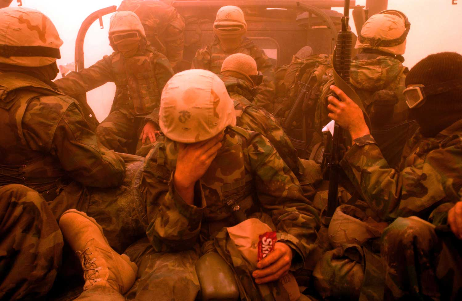 <b>James Hill, March 25, 2003                                   </b>                                   The only real resistance to the Allied invasion of Iraq in March 2003 turned out to be the weather, and in particular the sand storm that engulfed the troops for a full day in the middle of the desert about a week into the advance. Many of the Marines were stuck in open vehicles and they tried best to protect themselves from the biting wind laced with sand, all except this one Marine who steadfastly munched on his Skittles. A few years later this image was on the front of a book about the war and the Skittles had to be photoshopped out because of copyright violations for having the branded sweets on the cover! Looking back on that day I sense how the fog of the storm was also something of a metaphor for the whole campaign that even now it is hard to decide, even after the departure of American troops, what were the rights and wrongs and successes and failures of the campaign.