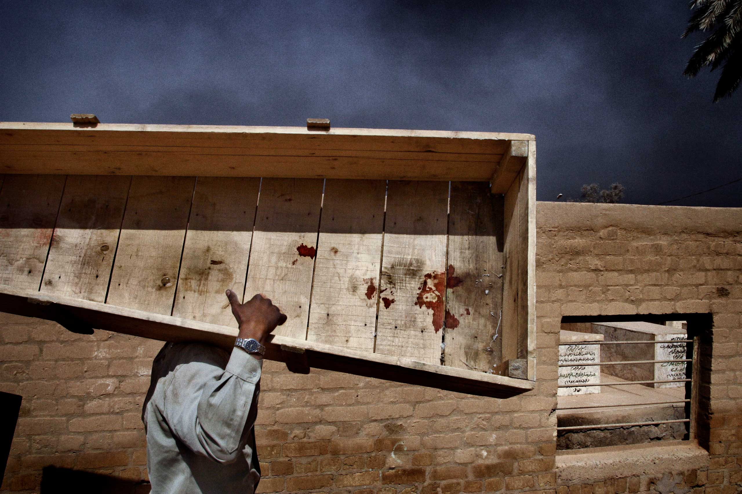 """<b>Yuri Kozyrev, March 31, 2003                                   </b>                                   A Sheikh Maaruf cemetery worker carries a reusable casket to the storage house after the funeral of Nidal Ali Jasem, a lonely deaf and dumb woman killed in a rocket blast in the south of Baghdad.                                    I was in Baghdad with a hundred journalists during """"Shock and Awe."""" When the operation began on March 21st, the prospect of dropping thousands bombs and missiles was frightening for everyone on the ground. On the first night, in spite of the thunderous explosions not far from the hotel the journalists were staying in, we observed that the weapons were destroying the targets with accuracy. After a week of bombings, it was amazing to witness the Iraqis' remarkable resilience. Most people continued with their daily lives as bombs continued to fall around them. And of course there were airstrikes where many Iraqi civilians were killed. We were being watched by minders all the time, who gave us access to the events they thought were news: civilians affected by the bombing or a press conference at the Ministry of Information. We were not allowed to go anywhere near the military or the Republican Guard. They wanted us to report their side of the story - we couldn't just get into the taxi and travel around.                                   It was late afternoon when my colleague, Sergey Loiko of the Los Angeles Times, our minder and I entered one of the oldest cemeteries in Baghdad. We didn't expect to see people there but there were some families who had brought the bodies of their relatives killed by airstrikes. A worker told us he had been busy all day long."""
