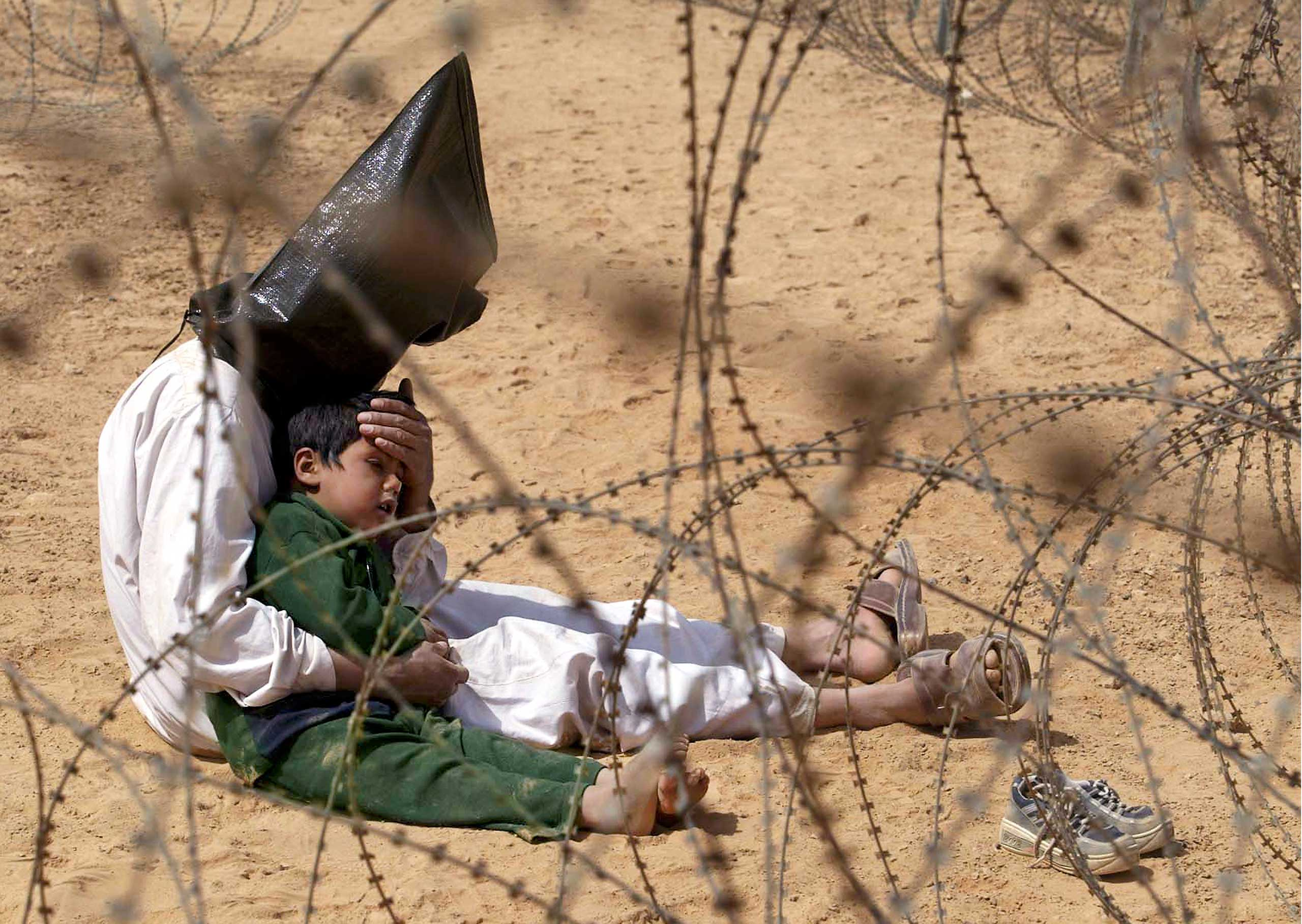 <b>Jean-Marc Bouju, March 31, 2003                                   </b>                                   Ten years ago. I doubt the desert remembers the barbed wire and hooded, shackled prisoners. Does it at least remember the screams of a boy clinging to a father who mumbled words of comfort from beneath a black sandbag? I hope the desert, too, felt relieved when an American soldier cut off the plastic handcuffs, and the man could finally embrace his child. But this desert has seen so much since the beginning of civilization that I do not think this was a remarkable day. This is not even a particularly noticeable war in the context of Iraq's 5,000 years of history.                                   But for me, this moment endures. The whole scene was surreal. This image was one of the last of my career. Three months later, I was disabled in a car accident. My daughter was the same age as the child in this photo. I look at her today and wonder what happened to that boy. I wonder why we were at war. What was accomplished? Ten years. An army of dead, wounded and mentally destroyed people. Maybe they, too, are wondering: why? I remember, and I wonder.