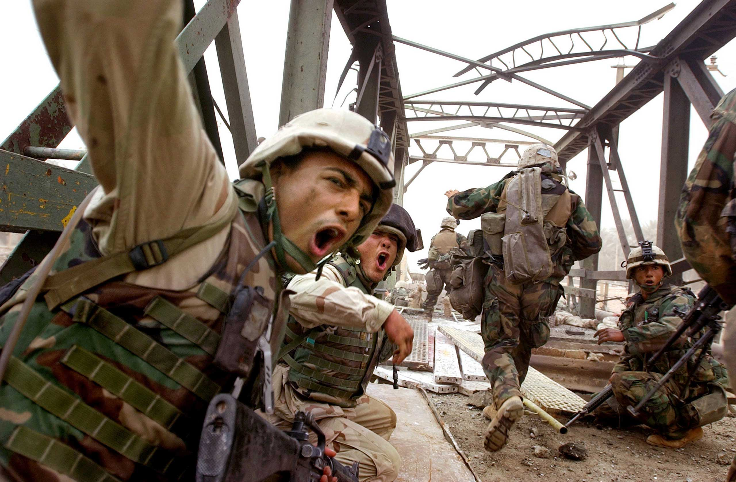 <b>Kuni Takahashi, April 7, 2003                                   </b>                                   The Iraqi army partially destroyed the bridge, which connected a suburb of Baghdad with the city center in an attempt to stop U.S. troops from advancing. The U.S. Marines decided to push ahead and sent engineers first. They laid iron plates down to patch holes on the bridge and began shouting at their fellow Marines to cross. There was heavy gunfire, but I wasn't sure which direction it was coming from. I just ducked my head down and followed the Marines. It was one of the first encounters with the Iraqi army and it gave me a sense that the fighting would intensify. Fortunately, my guess was wrong and the Marines reached the center in three days and took down Saddam Hussein's statue.
