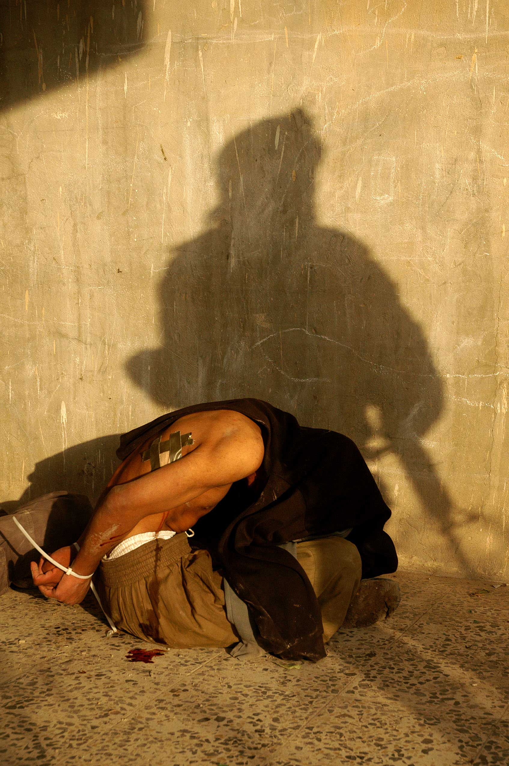 <b>Ashley Gilbertson, Nov. 13, 2004                                   </b>                                   Of all the images that I made in the six years I spent working in Iraq, this is the photograph that best represents my experience of war. The anonymous nature of the picture speaks to how we fight war. The shadow of the Marine on the wall is merely a symbol: of American force and of policies made in Washington and carried out in the Middle East. When insurgents kill U.S. forces, they are not trying to murder Demarkus Brown, a young man from a small town whose parents loved him more than anybody else in the world. They were hoping to kill the symbol, to damage American ideals. The insurgent on the ground with his face covered by a sweater is as impersonal as the MarineÕs shadow. When the American military fights their enemy, they become just that: the enemy. Aiming through his rifle's iron sights, a soldier isn't seeing Mohammad Rezzaq, a father with four children waiting at home, he only sees AQI (al Qaeda in Iraq) or a Mahdi army fighter. To personalize killing would make it far more difficult to pull the trigger and perhaps impossible to wage war on a large scale. Rendering 'The Other' anonymous is how we bring ourselves to fight.