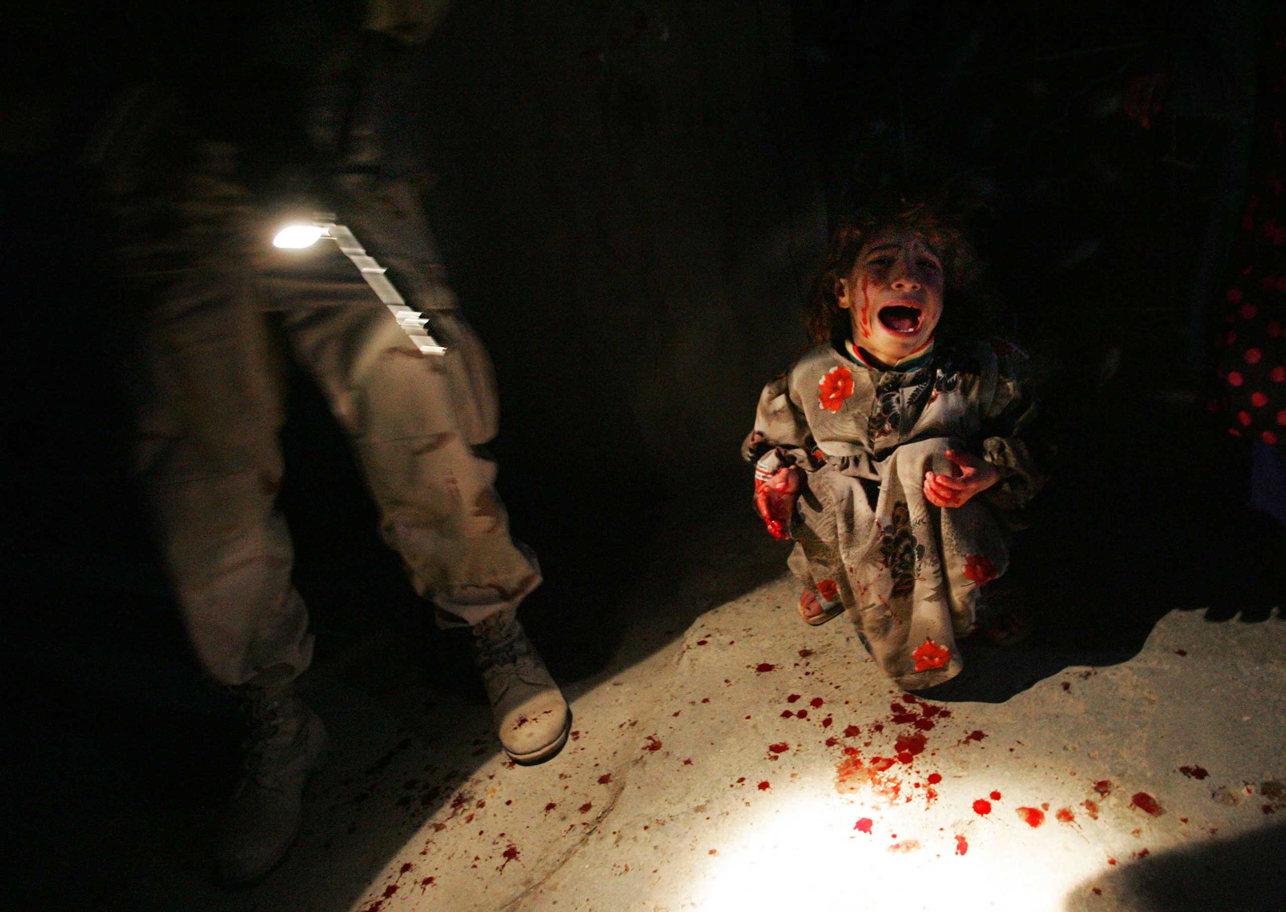 """<b>Chris Hondros, Jan. 18, 2005                                   </b>                                   <i>The following is an excerpt written by Chris Hondros about his photograph. The writing was pulled from his laptop recovered after he was killed on assignment in Libya. </i>                                                                      At six in Tal Afar, it isn't yet quite dark. A gloom hung over the roads and alleys with just a little dark blue light from the sky. No one was out. As we made our way up a broad boulevard, in the distance I could see a car making its way toward us. With all the relentless car bombings in Iraq, groups of soldiers are understandably nervous about any cars that approach them, and they do not allow private cars to breech the perimeter of their foot patrols, particularly at night. """"We have a car coming,"""" someone called out, as we entered an intersection. We could see the car about a 100 meters down but I doubt if it could see us—it would be hard to see this group of darkly camouflaged men in the gloom. That already gave me a bad feeling about what might conspire, so I moved over to the side of the road, out of anyone's line of fire. The car continued coming; I couldn't see it anymore from my perch but could hear its engine now, a high whine that sounded more like acceleration than slowing down. It was maybe 50 yards away now.                                    """"Stop that car!"""" someone shouted out, seemingly simultaneously with someone firing what sounded like warning shots—a staccato measured burst. The car continued coming. And then perhaps less than a second later a cacophony of fire, shots rattling off in a chaotic overlapping din. The car entered the intersection on its momentum and still shots were penetrating it and slicing it. Finally the shooting stopped, the car drifted listlessly, clearly no longer being steered, and came to a rest on a curb. I stared at it in shocked silence. Soldiers began to approach it warily. Th"""