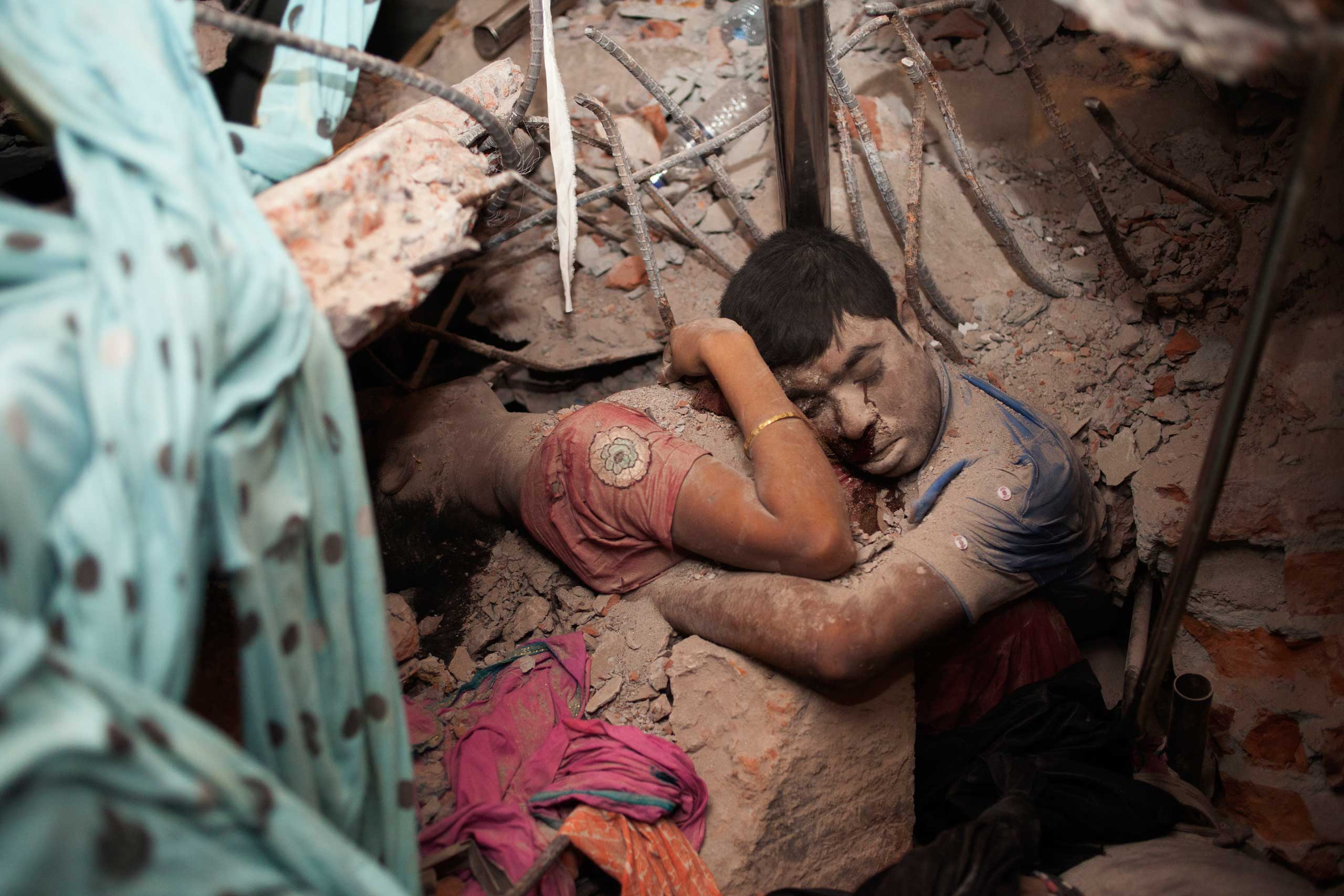 April 25, 2013. Two victims amid the rubble of a garment factory building collapse in Savar, near Dhaka, Bangladesh.