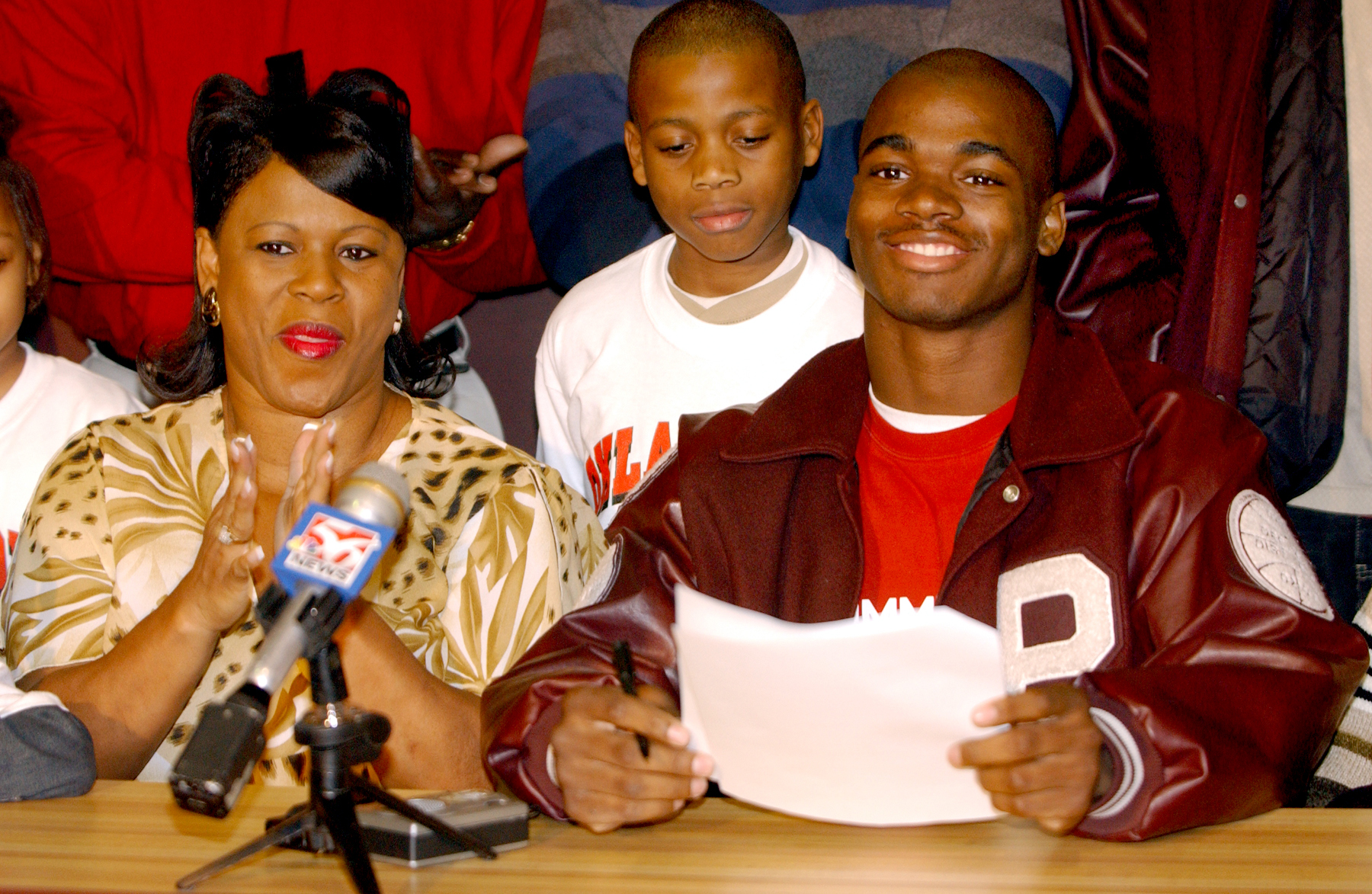 Palestine running back Adrian Peterson, right, smiles after signing a national letter of intent to play football for Oklahoma on Feb. 4, 2004, in Palestine, Texas. At left is his mother Bonita Jackson, and at center is his brother, Jaylon Jackson.