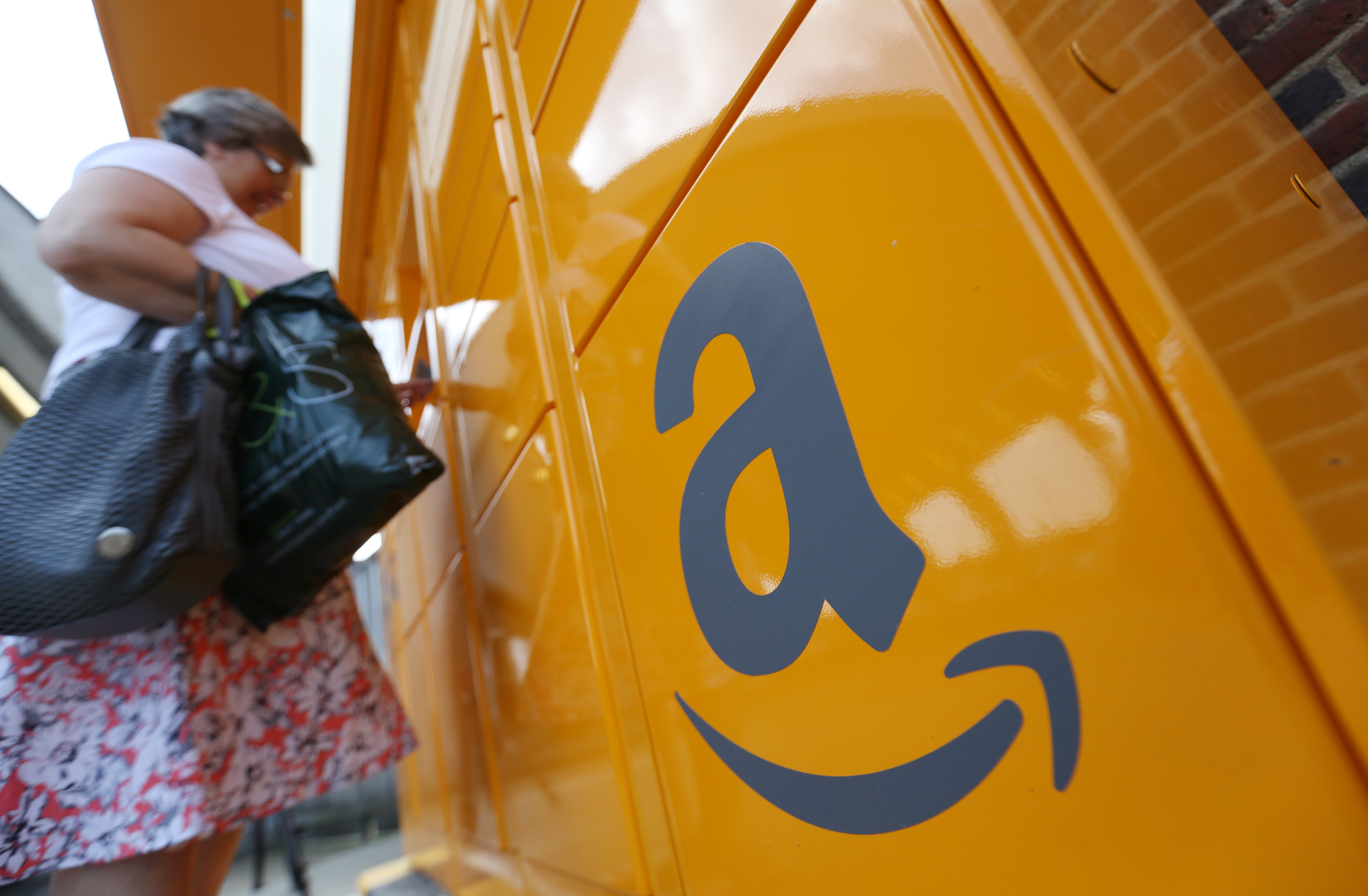 The Amazon logo sits on an Amazon.com Inc. pickup and collect locker as a customer collects an online purchase at Newbury Park railway station in Newbury Park, U.K., on Wednesday, July 23, 2014.