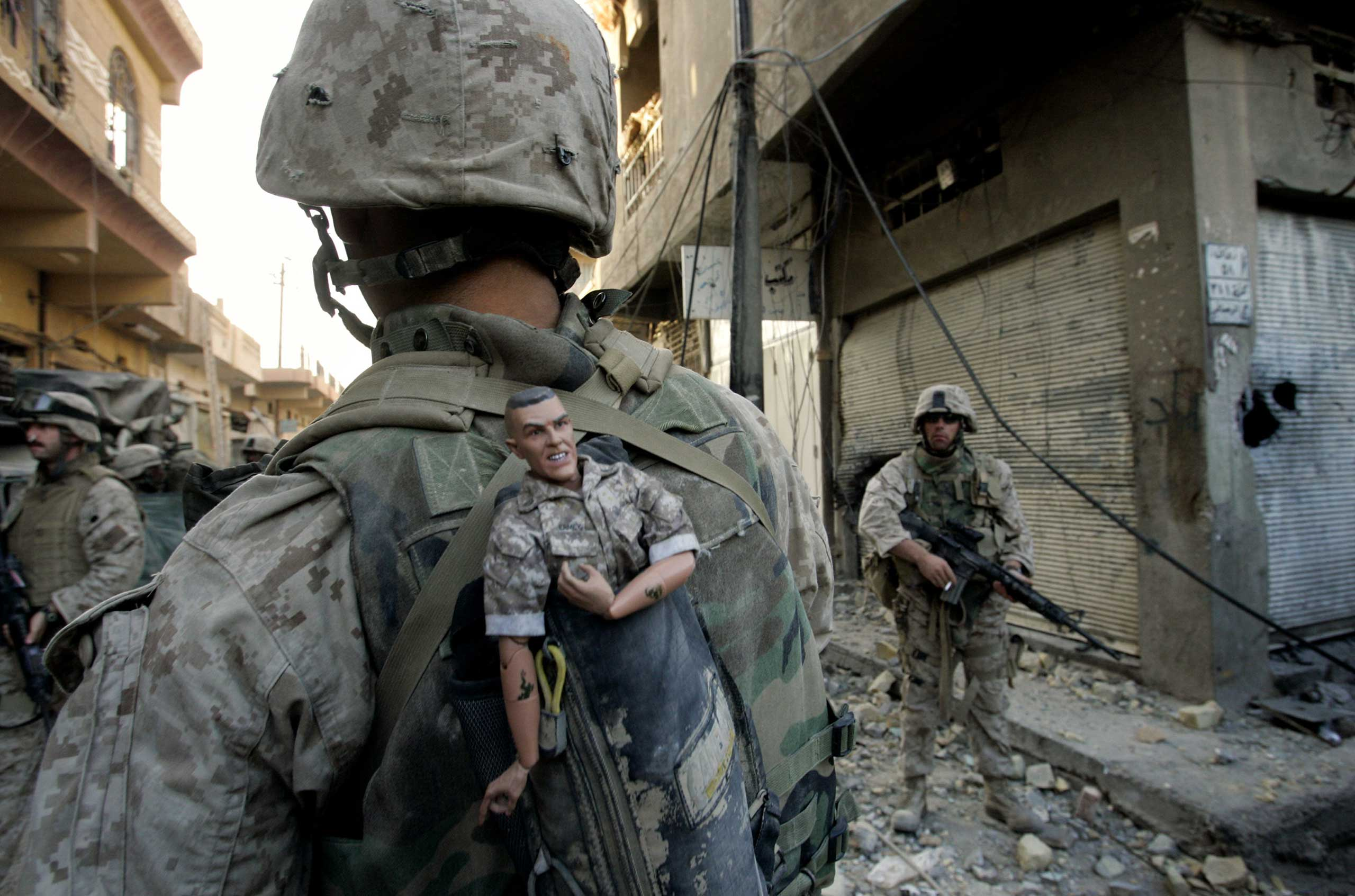 A U.S. Marine of the 1st Division carries a mascot for good luck in his backpack as his unit pushed further into the western part of Fallujah, Iraq, Nov. 14, 2004.