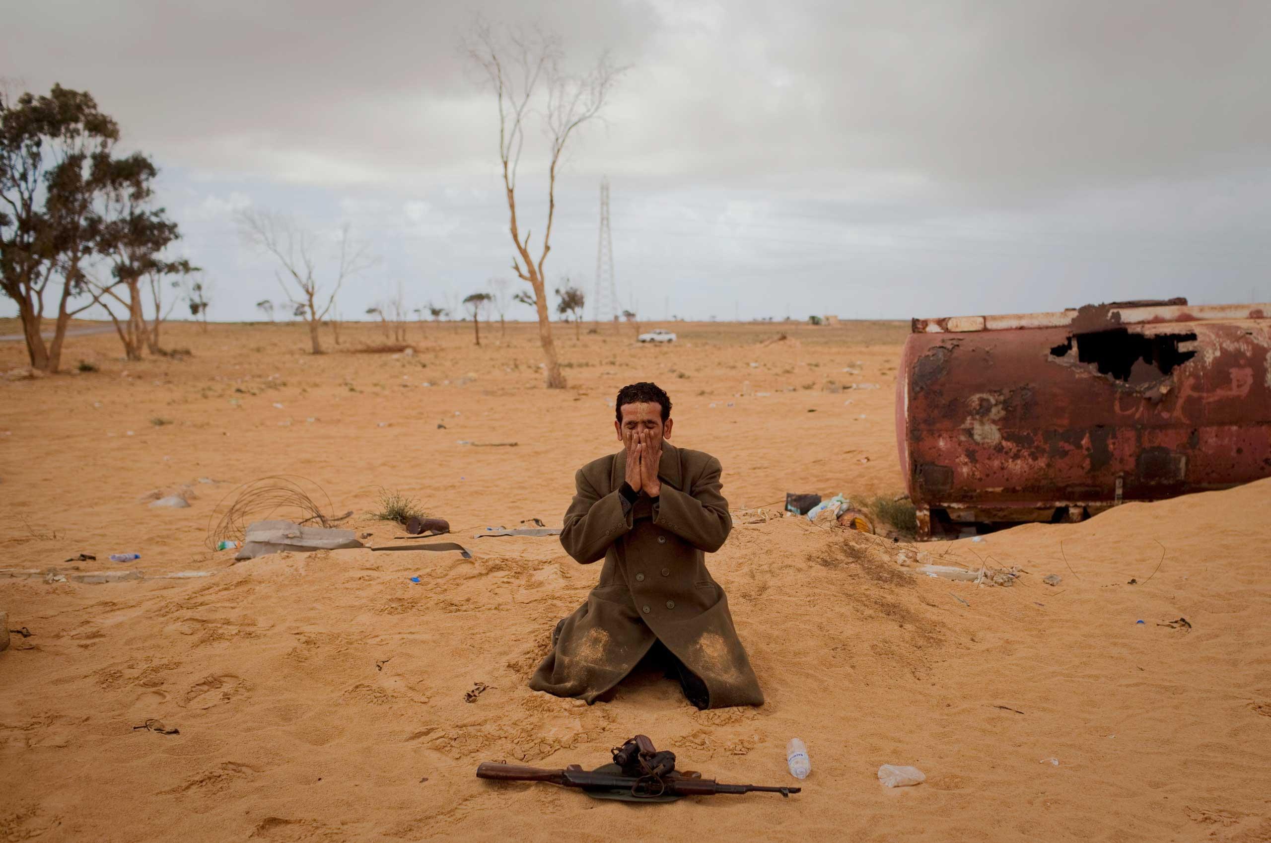 A Libyan rebel prays next to his gun on the frontline of the outskirts of the city of Ajdabiya, south of Benghazi, eastern Libya, March 21, 2011.