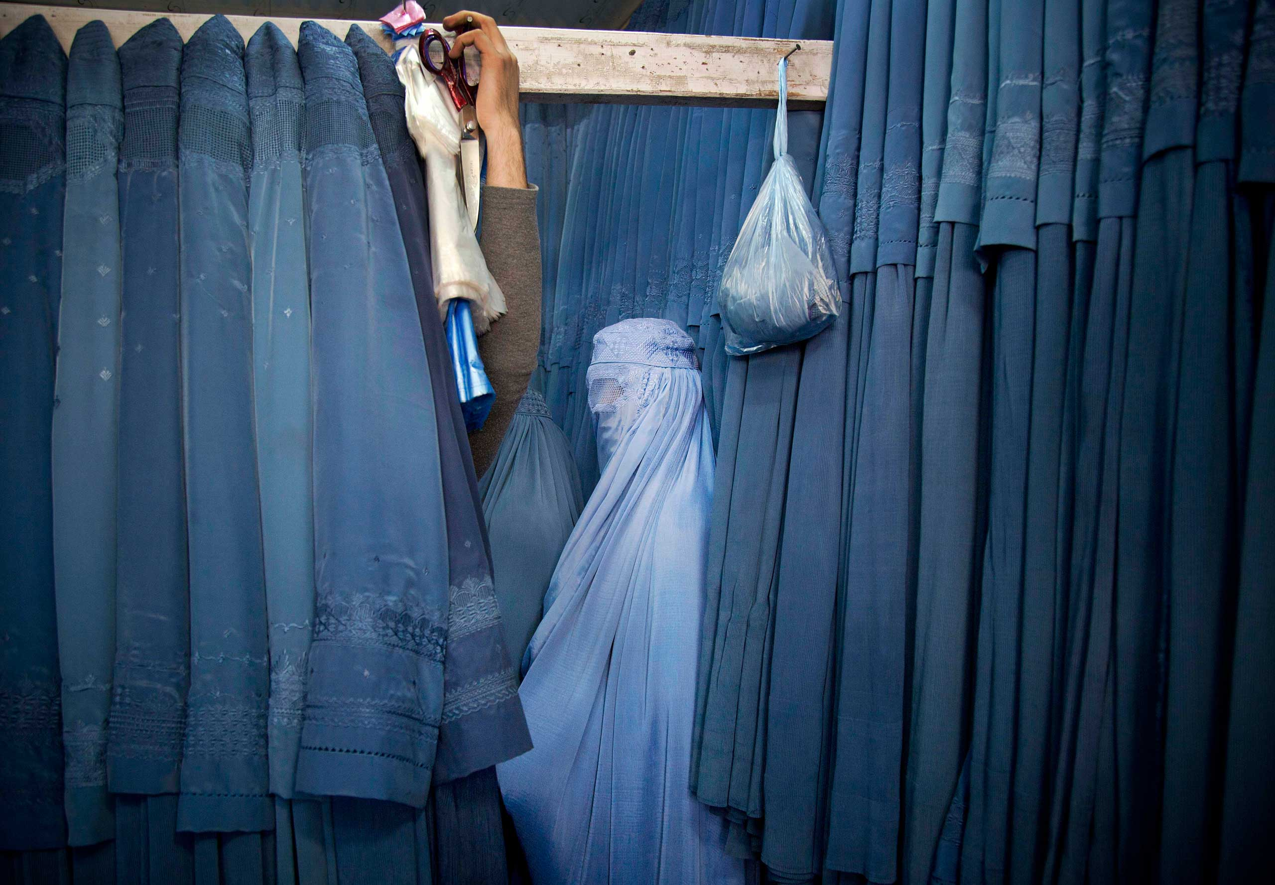 An Afghan woman waits in a changing room to try out a new Burqa, in a shop at in the old city of Kabul, April 11, 2013.