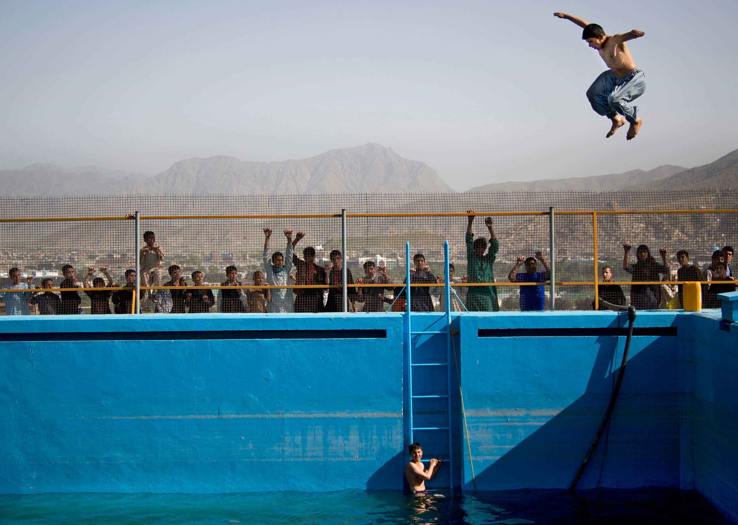 An Afghan man jumps from a diving board into a swimming pool on a hill overlooking Kabul, Afghanistan, Friday, May 17, 2013.