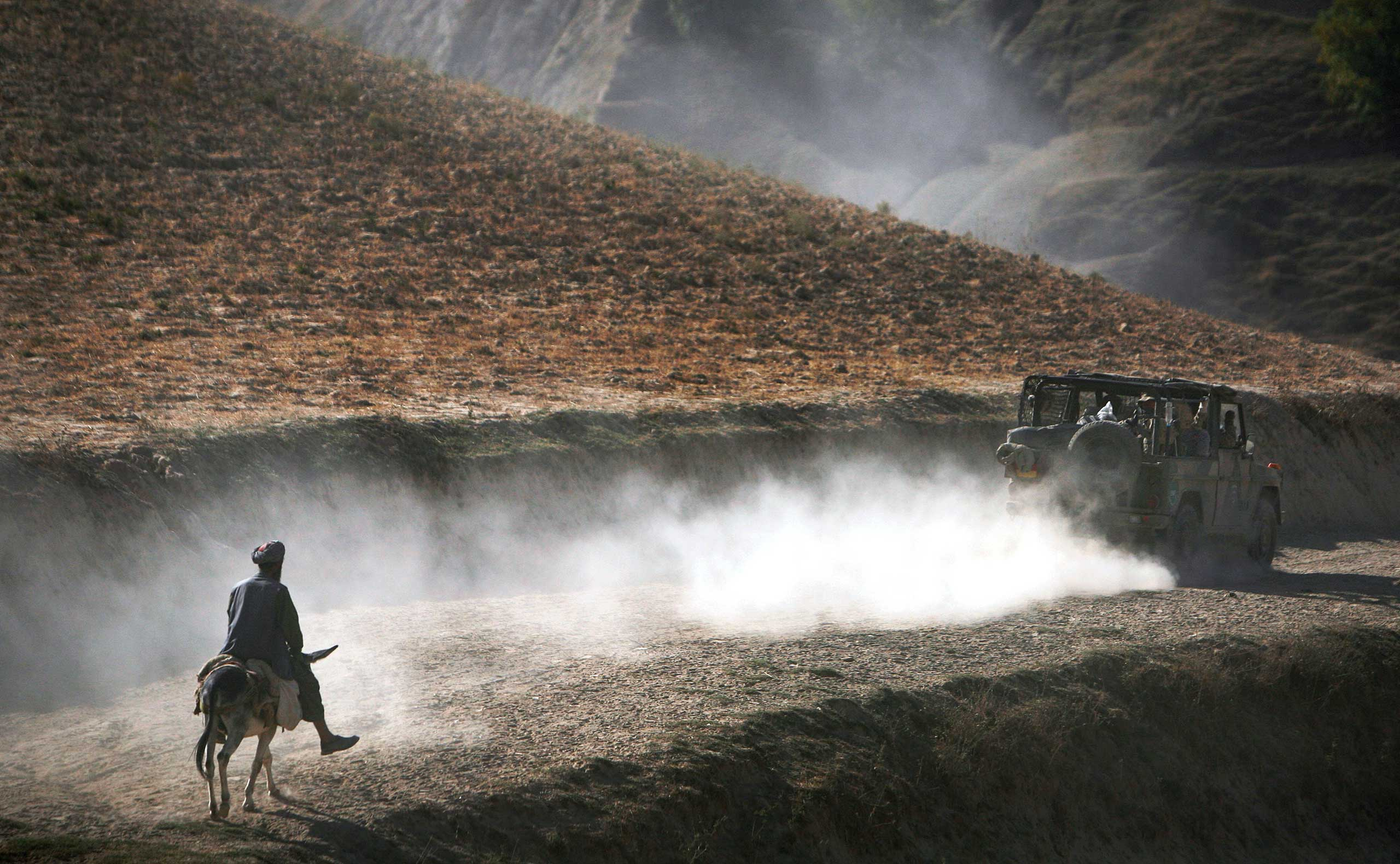 An Afghan man on his donkey follows a convoy of German ISAF soldiers patrolling Yaftal E Sofla, in the mountainous region of Feyzabad, on Sept. 15, 2009, east of Kunduz, Afghanistan.