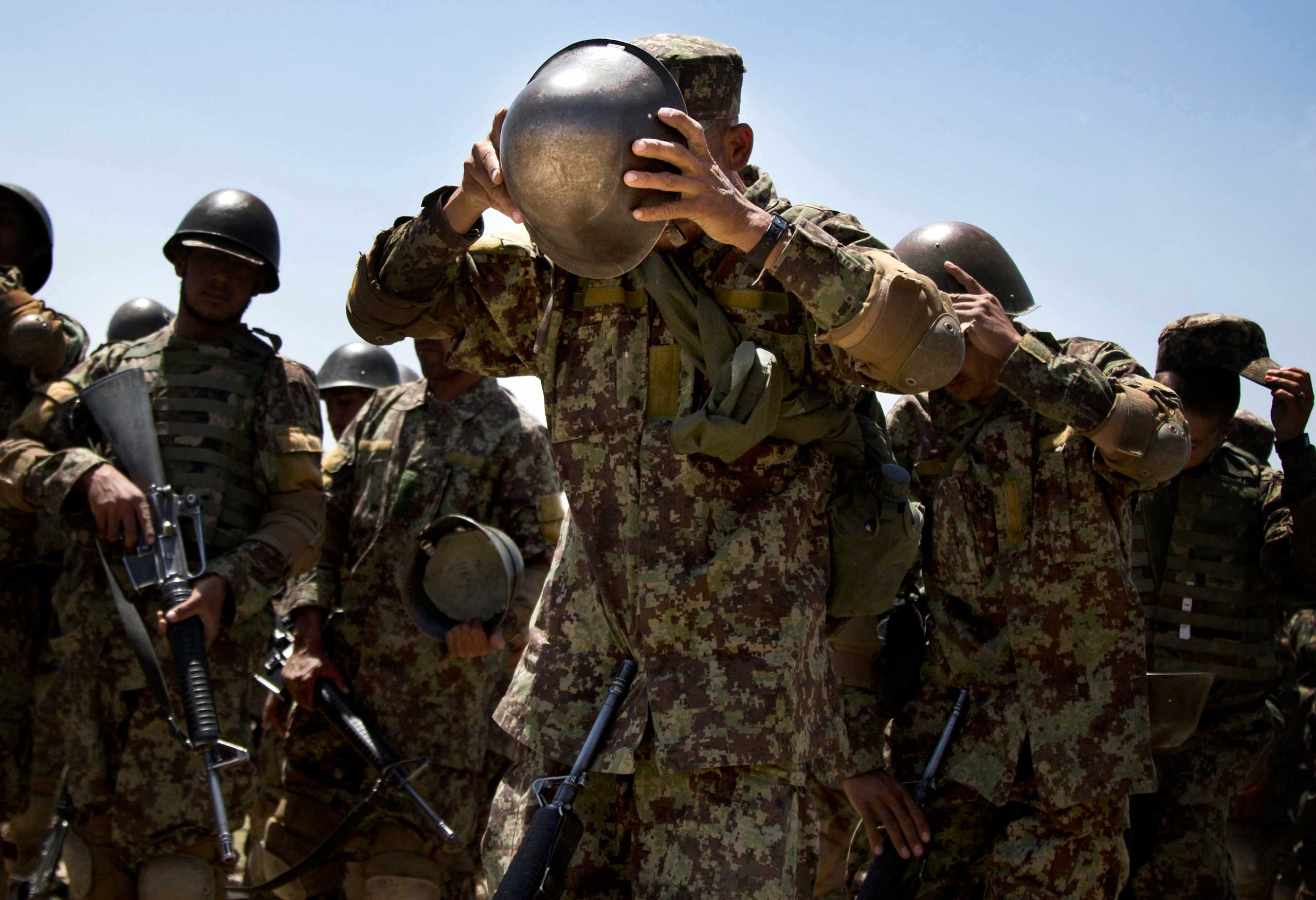 An Afghan Army soldier adjusts his helmet at a training facility on the outskirts of Kabul, May 8, 2013.