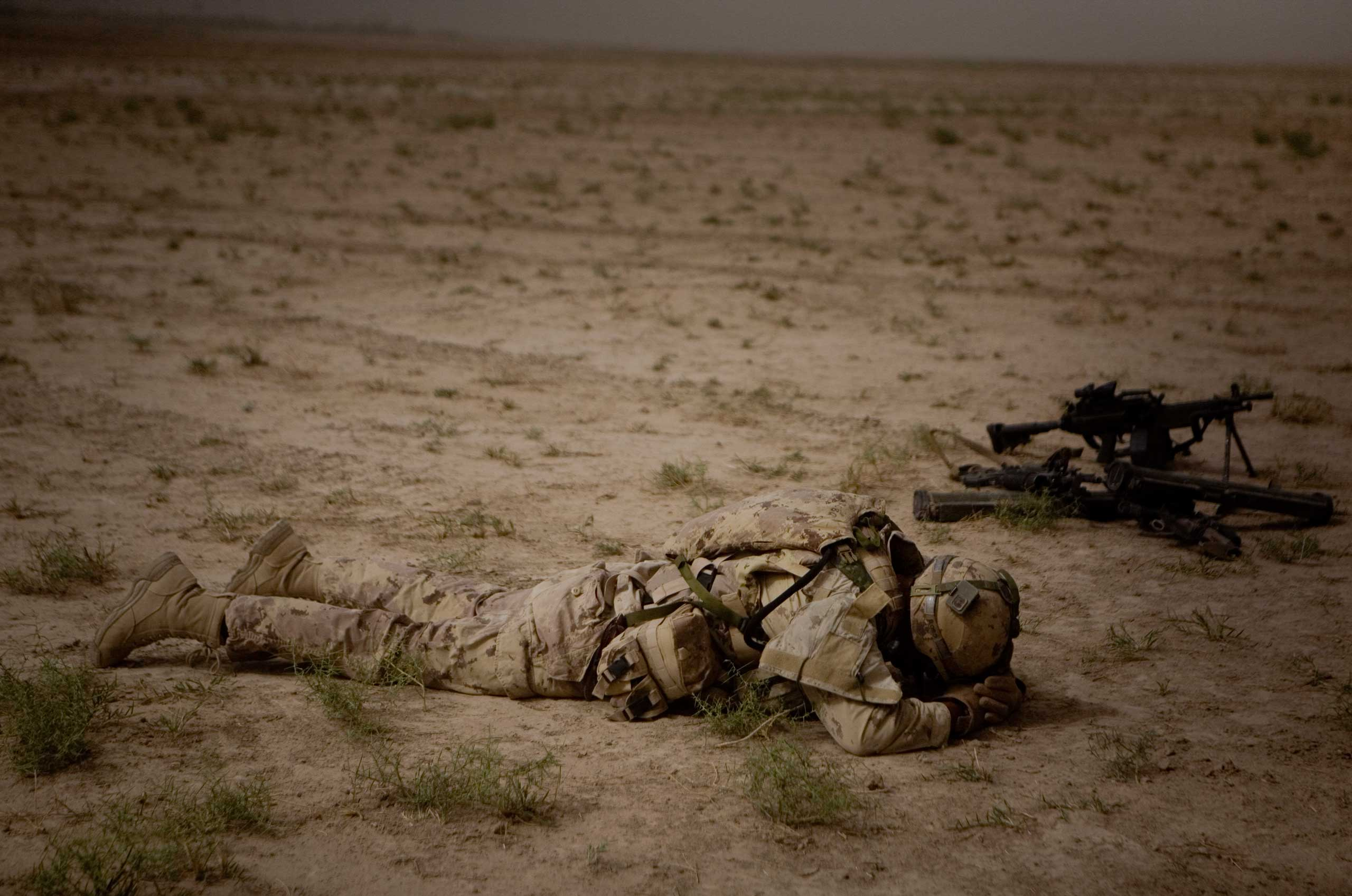 A Canadian soldier with the 1st Battalion, The Royal Canadian Regiment rests next to his guns after a mission in Khebari Ghar in the Panjwayi district, south-west of Kandahar, Afghanistan, June 3, 2010.