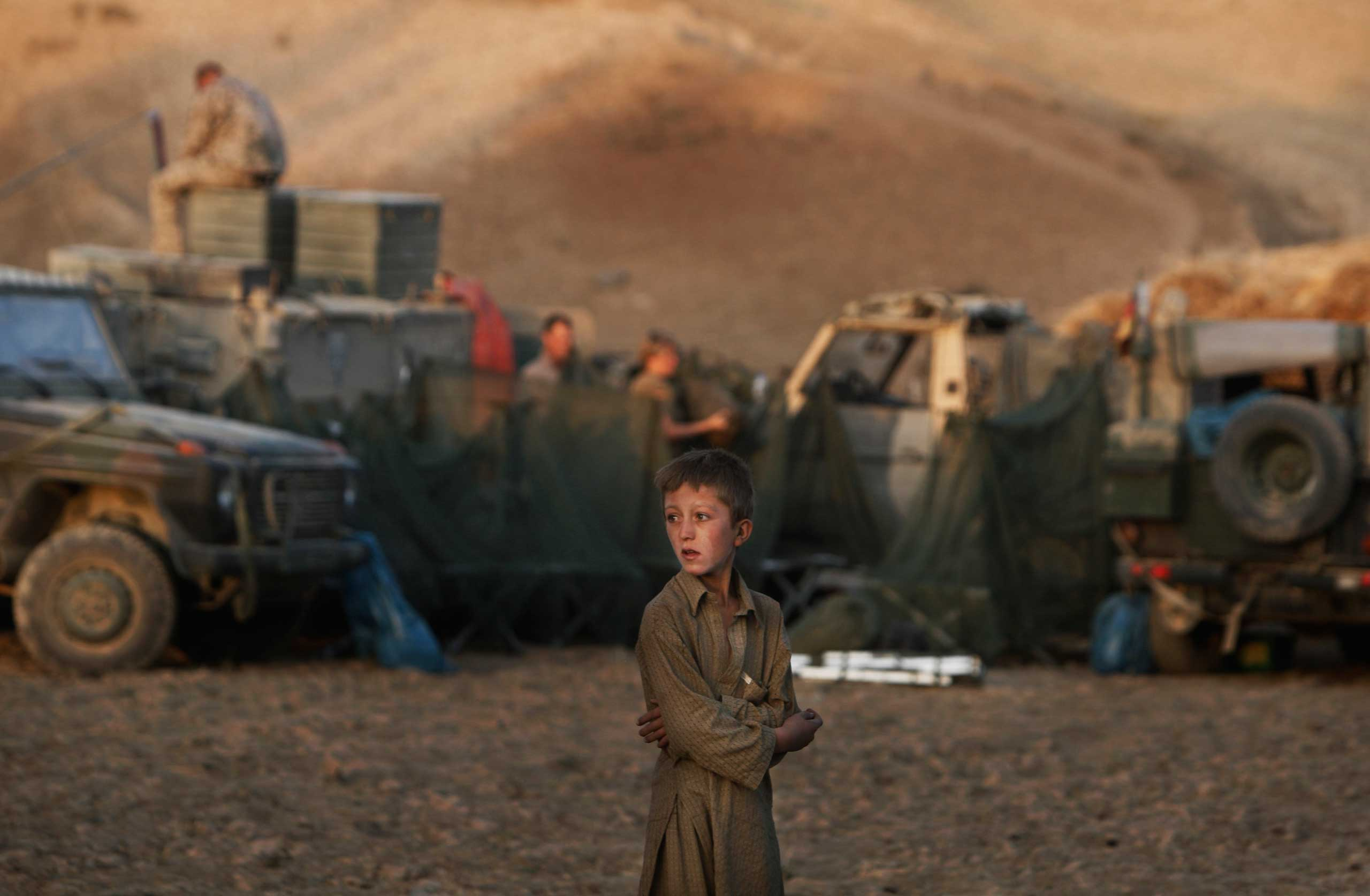 An Afghan boy looks on as German ISAF soldiers prepare a temporary camp to overnight during a long term patrol in the mountainous region of Feyzabad, east of Kunduz, Afghanistan, Sept. 14, 2009.