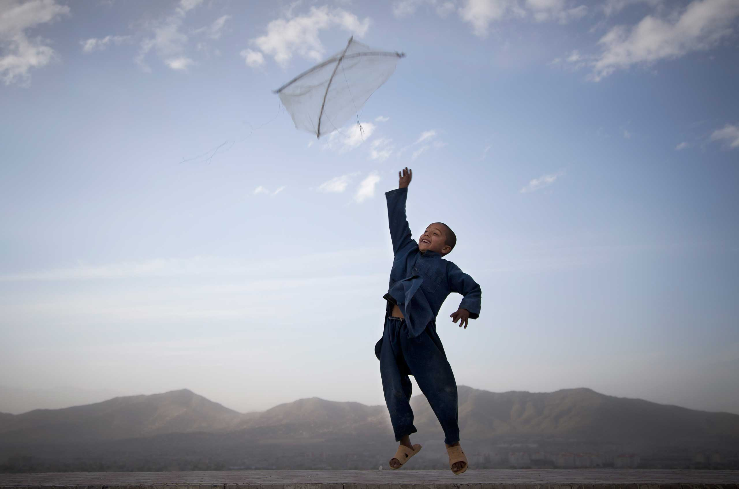 An Afghan boy flies his kite on a hill overlooking Kabul, Afghanistan, May 13, 2013.