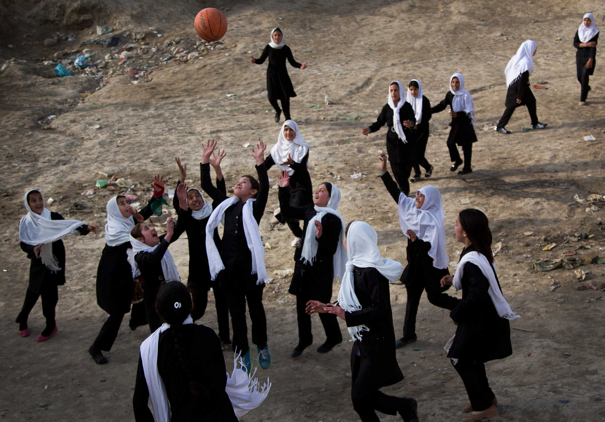 Afghani schoolgirls play volleyball with a basketball during a break at their girls school in the old town of Kabul, April 7, 2013.