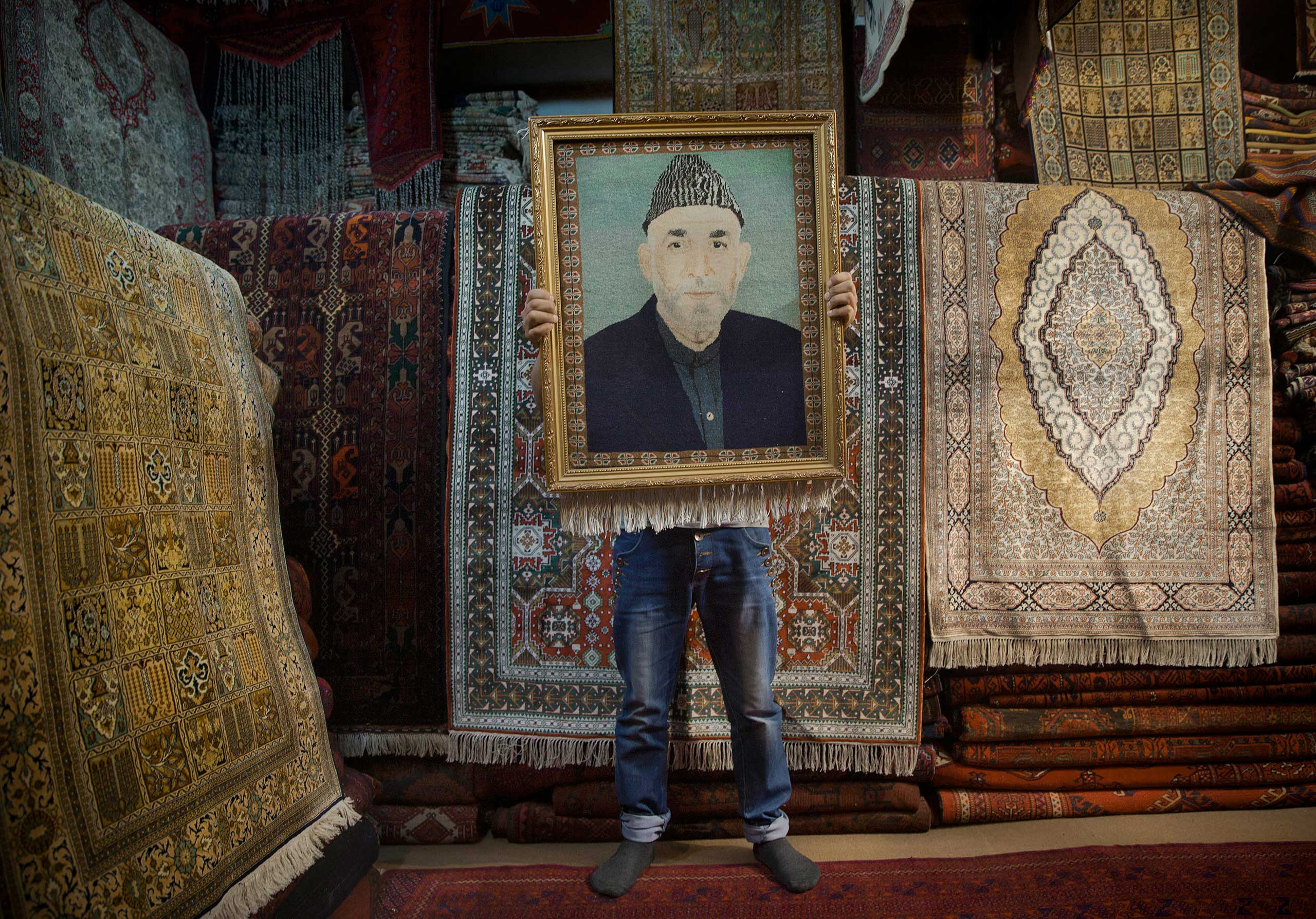 An Afghan carpet seller holds up a framed carpet depicting Afghan President Hamid Karzai in his store in Kabul, March 30, 2014.