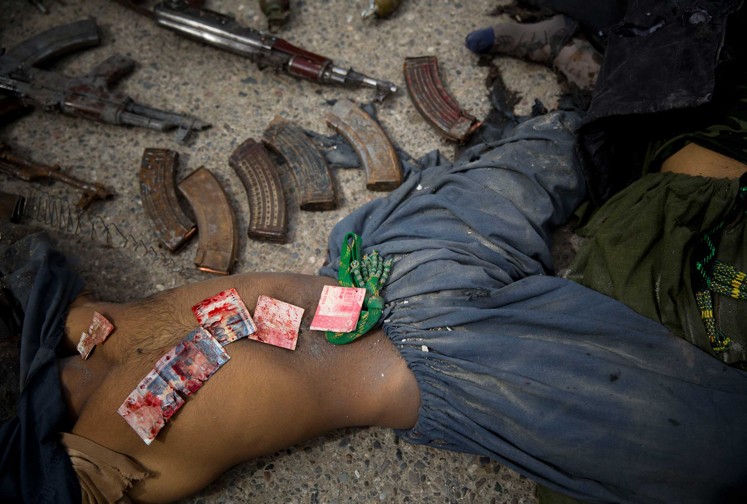 Pakistani bank notes covered in blood are displayed on the body of a dead suicide bomber after police found them in his pocket in the center of Kandahar, Afghanistan, March 12, 2014, after an attack on the former Afghan intelligence headquarters.