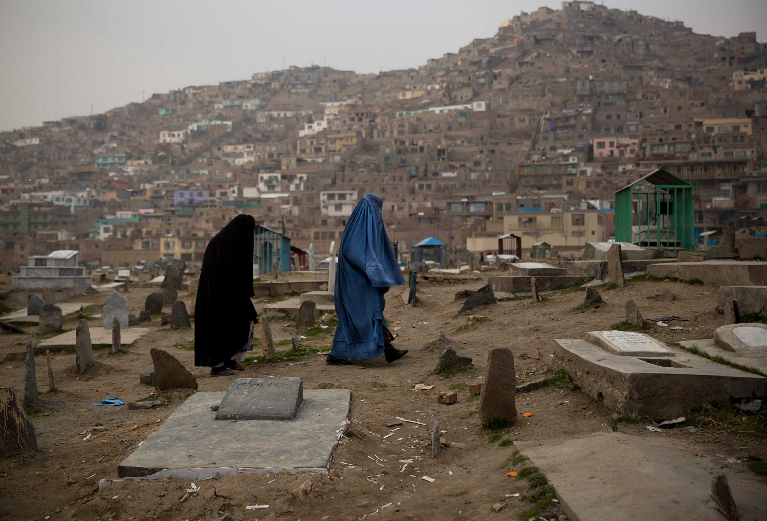 Afghan women cross a cemetery in the center of Kabul, March 7, 2014.