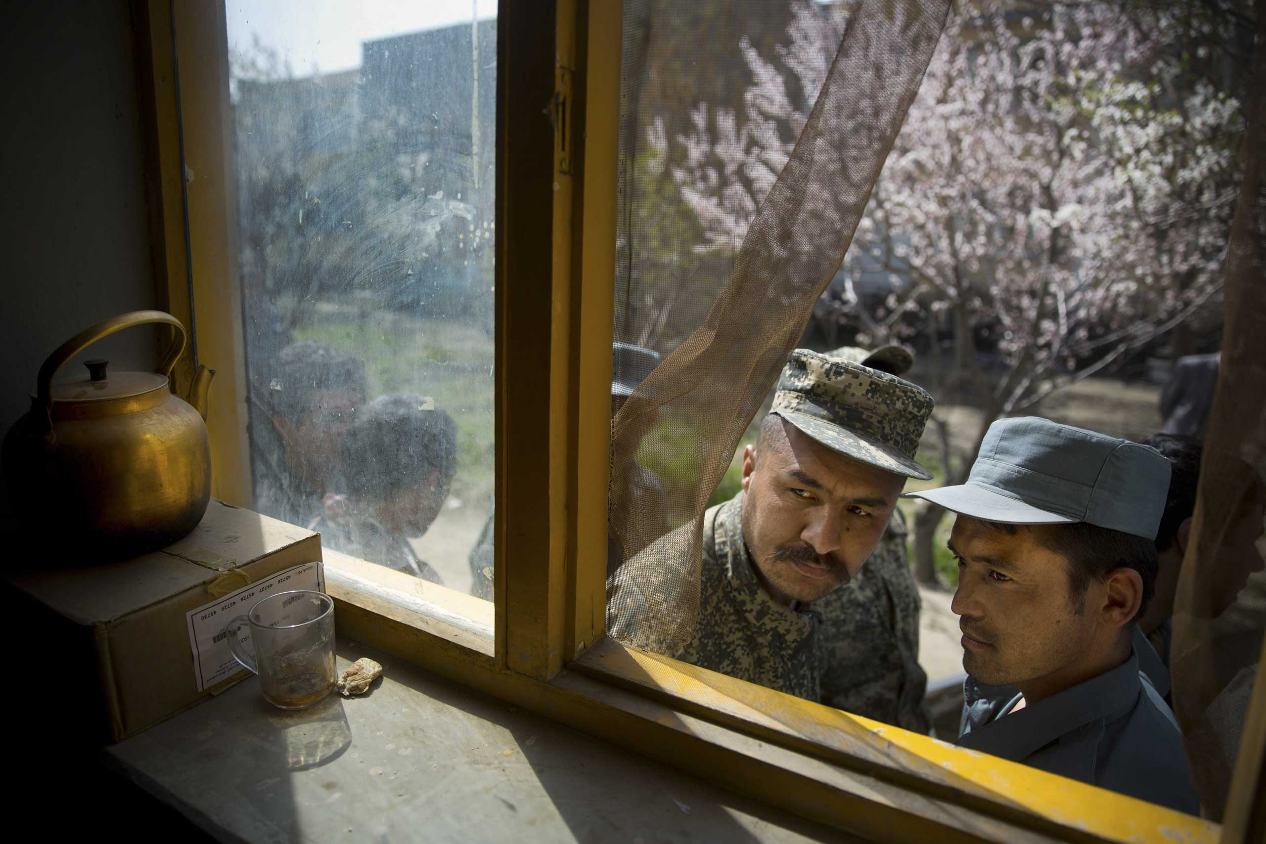 An Afghan soldier, left, and a police man peek through a window as they queue with others to get their registration card on the last day of voter registration for the upcoming presidential elections outside a school in Kabul, April 1, 2014.