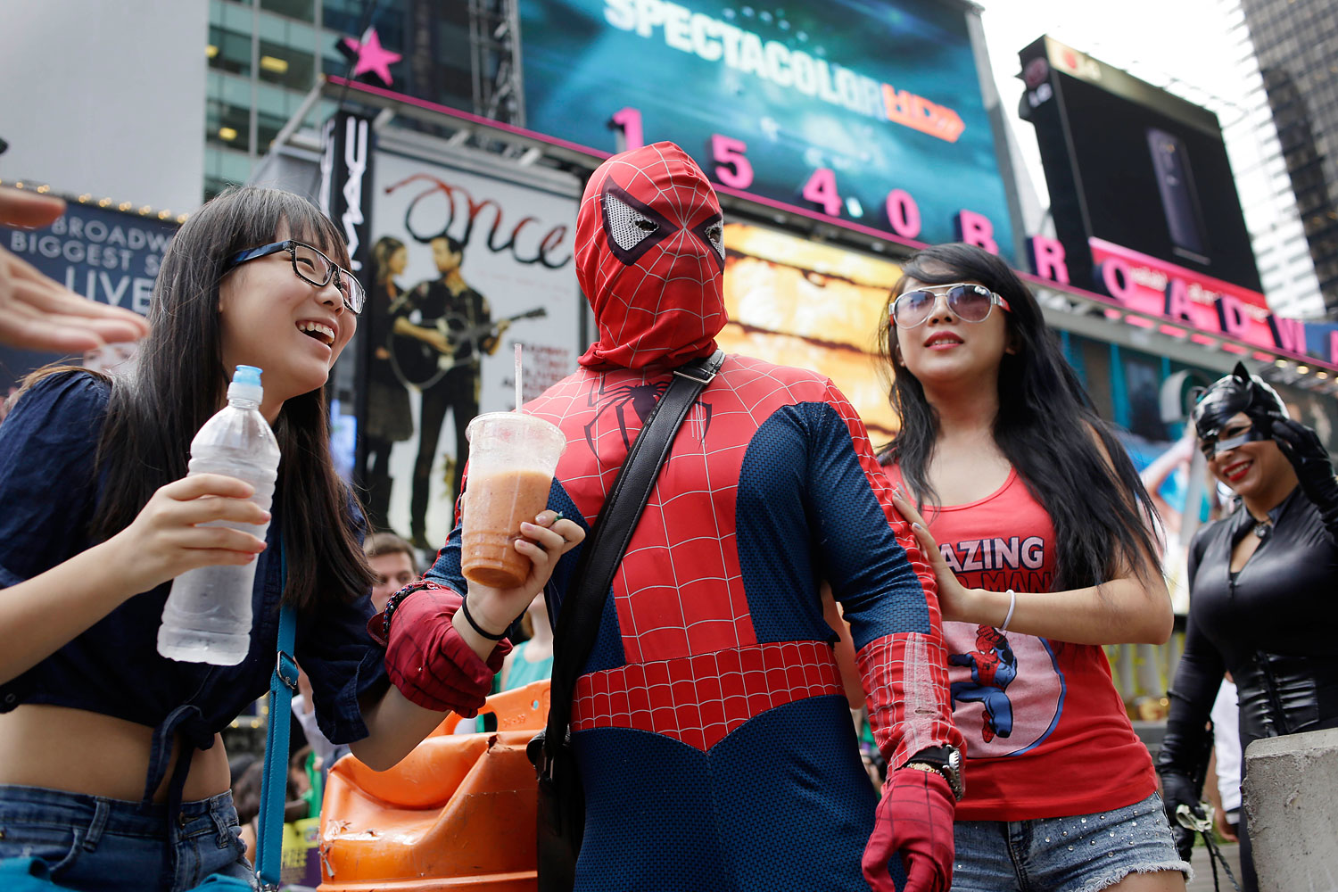 A performer dressed as Spiderman poses with tourists in Times Square, July 28, 2014 in New York. Two costumed performers, dressed as Spiderman and Batman, were charged with misdemeanor assault after an incident with a heckler in Times Square, New York, Sept. 14, 2014.