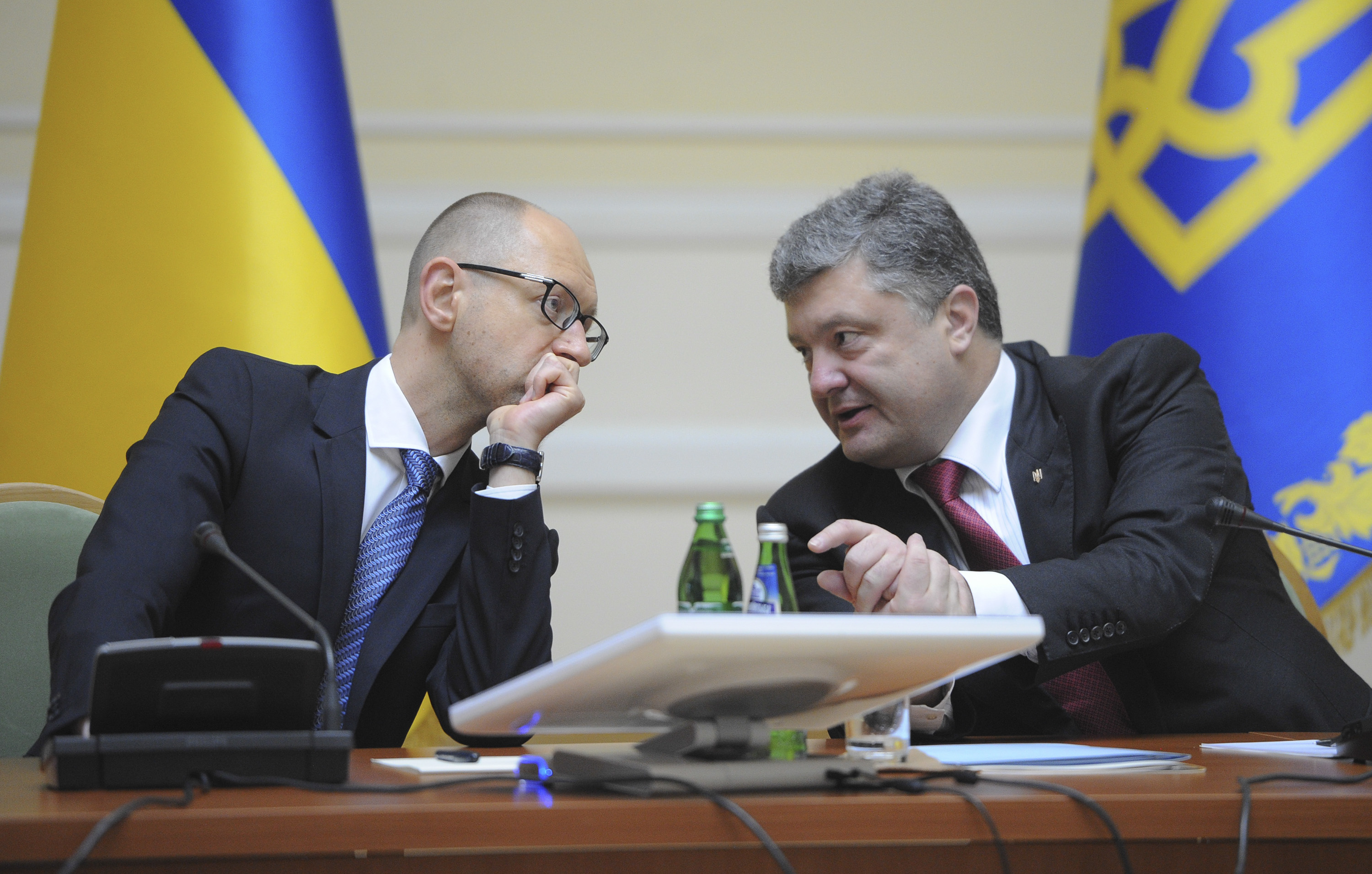Ukrainian President Petro Poroshenko, right, talks with Prime Minister Arseniy Yatsenyuk in Kiev, Ukraine,  on Sept. 10, 2014. Poroshenko promised on that day to introduce to parliament as early as next week a bill that would offer greater autonomy to rebellious regions in the pro-Russia eastern regions, where separatists have been battling government troops for almost five months