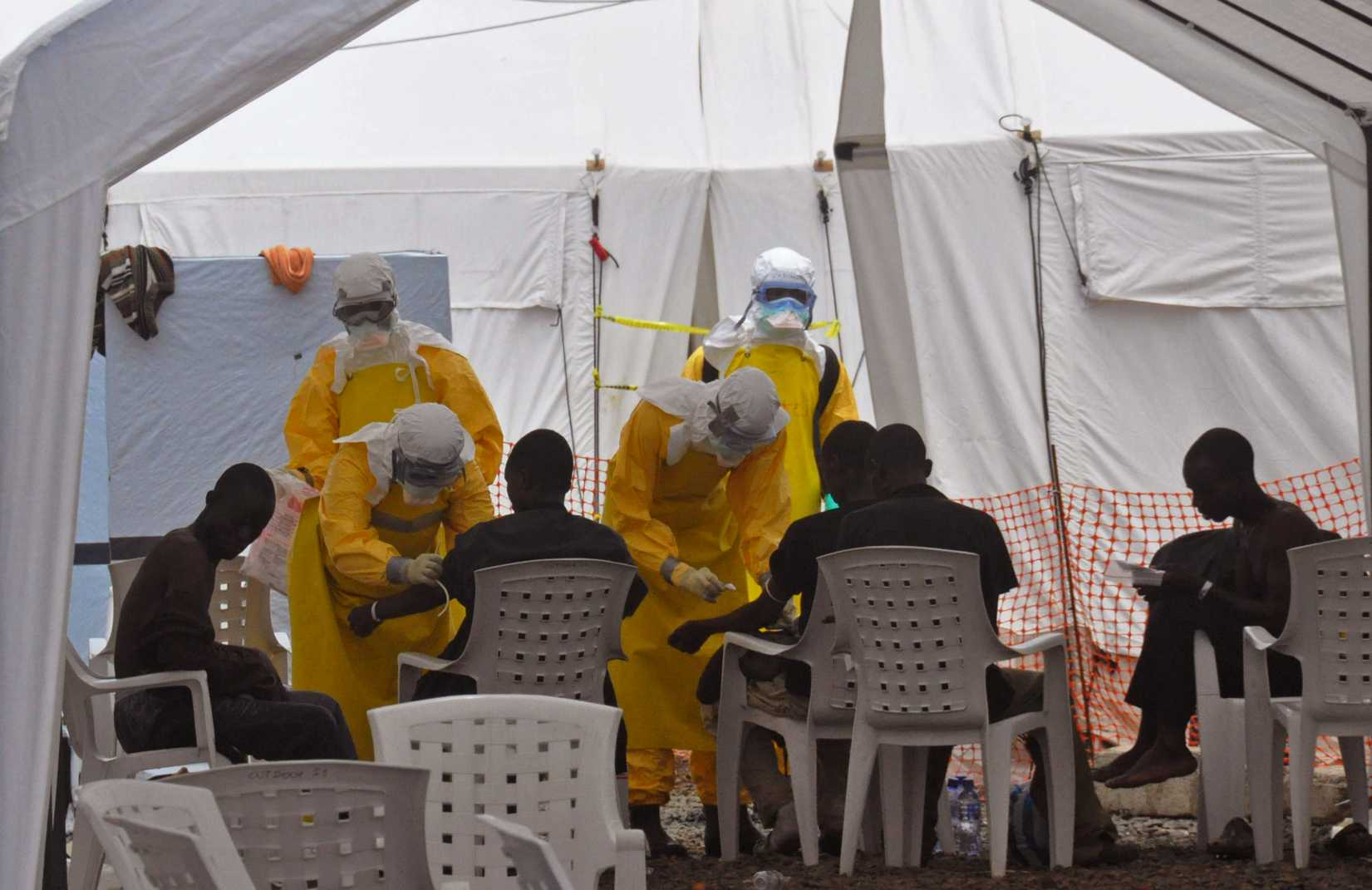 Health workers, attend to patients that contracted the Ebola virus, at a clinic in Monrovia, Liberia, Monday, Sept. 8, 2014.