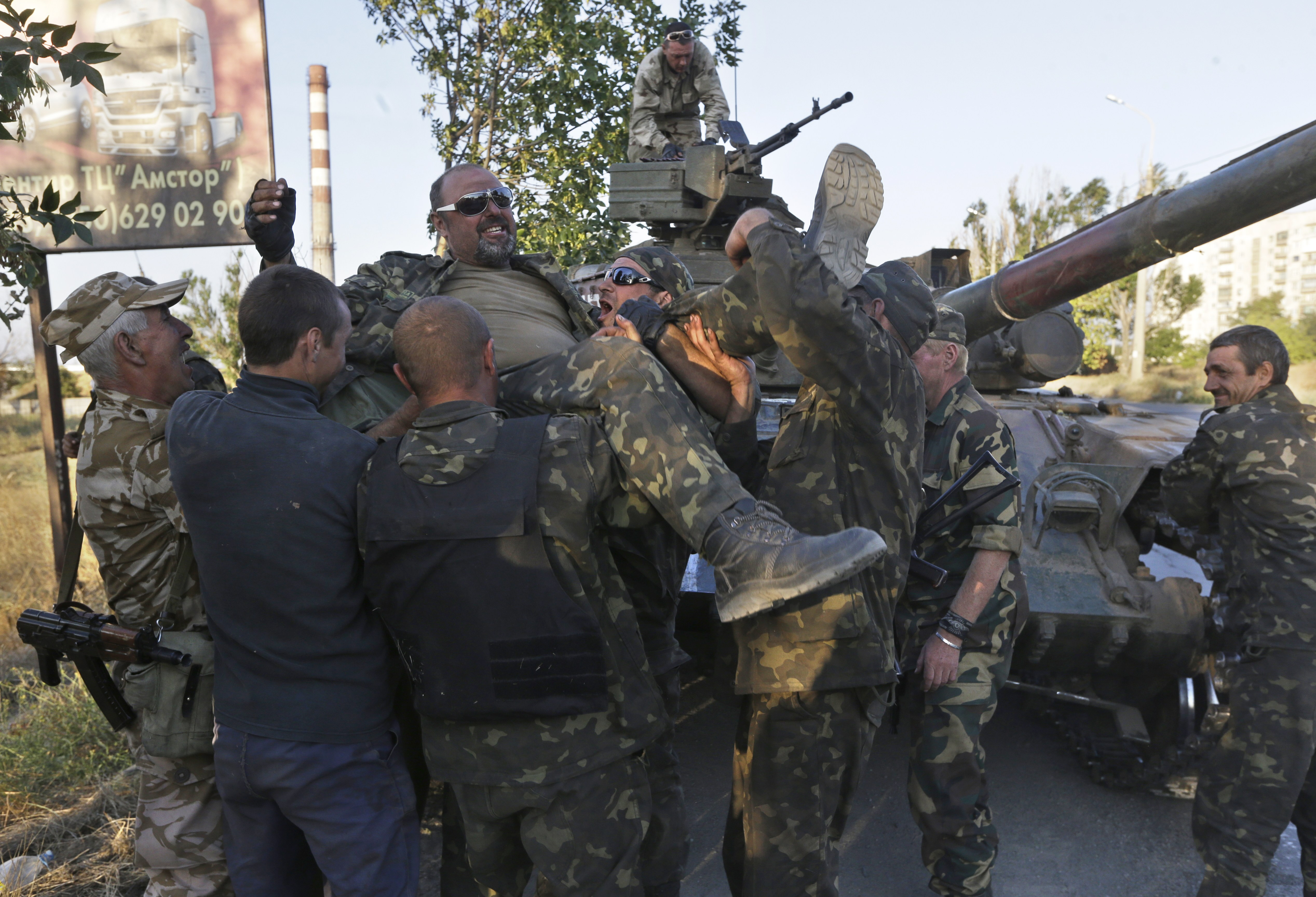 Ukrainian army soldiers congratulate their comrade who returned alive from the battlefield in the port city of Mariupol, southeastern Ukraine, Friday, Sept. 5, 2014, shortly after the announcement of a ceasefire between the government and Russian-backed separatist rebels.
