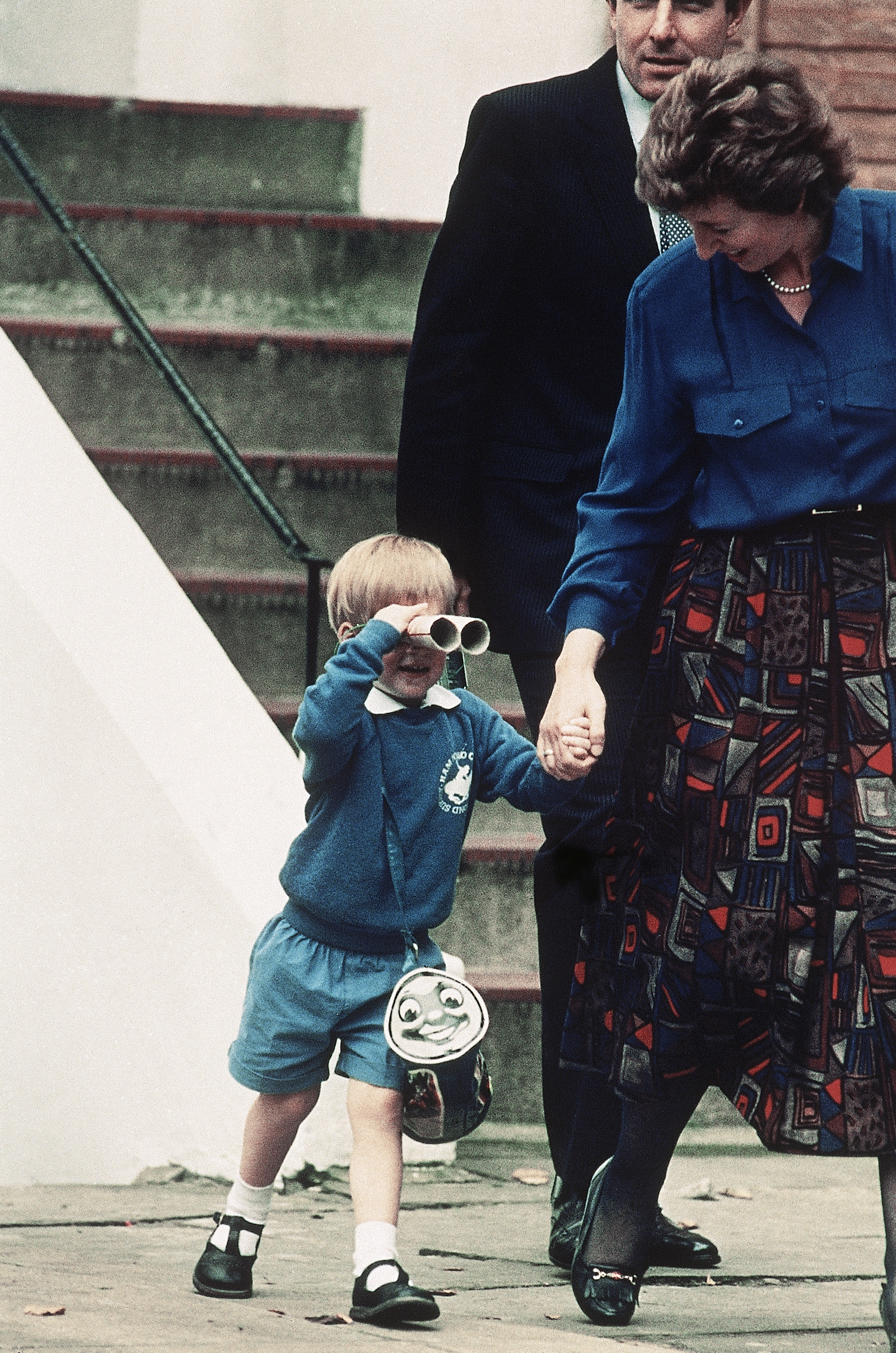 Prince Harry, 3, peers through a pair of  binoculars made with two cardboard tubes on his way out from his first day at a kindergarten in London on Sept. 16, 1987.