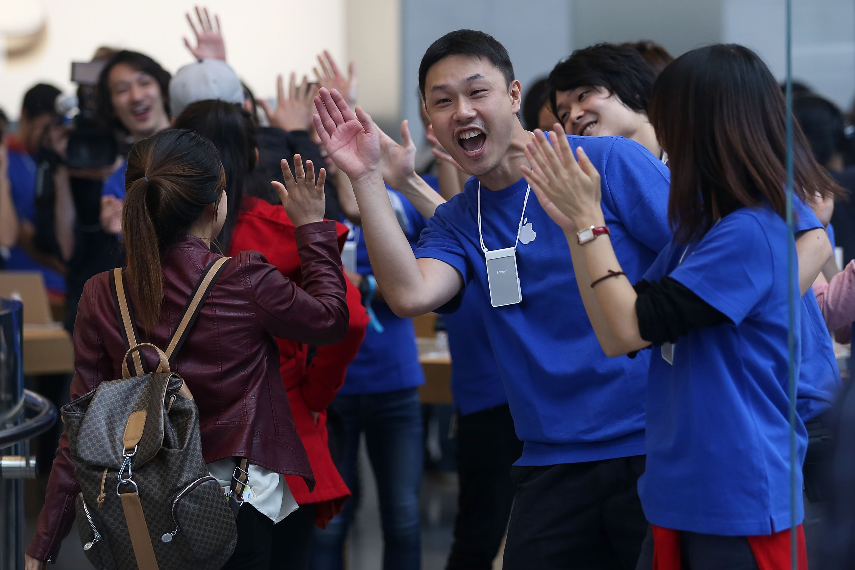 Apple store staff high five customers as they enter an store in Tokyo on Sept. 19, 2014.
