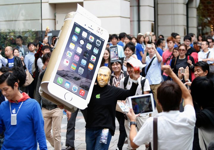 A man wearingaA man wearing a mask depicting Apple's co-founder Steve Jobs holds up a cardboard cut-out of Apple's new iPhone 6, as he walks into the Apple Store in Tokyo on Sept. 18, 2014. a mask depicting Steve Jobs holds up a cardboard cut-out of Apple's new iPhone 6, as he walks into the Apple Store in Tokyo