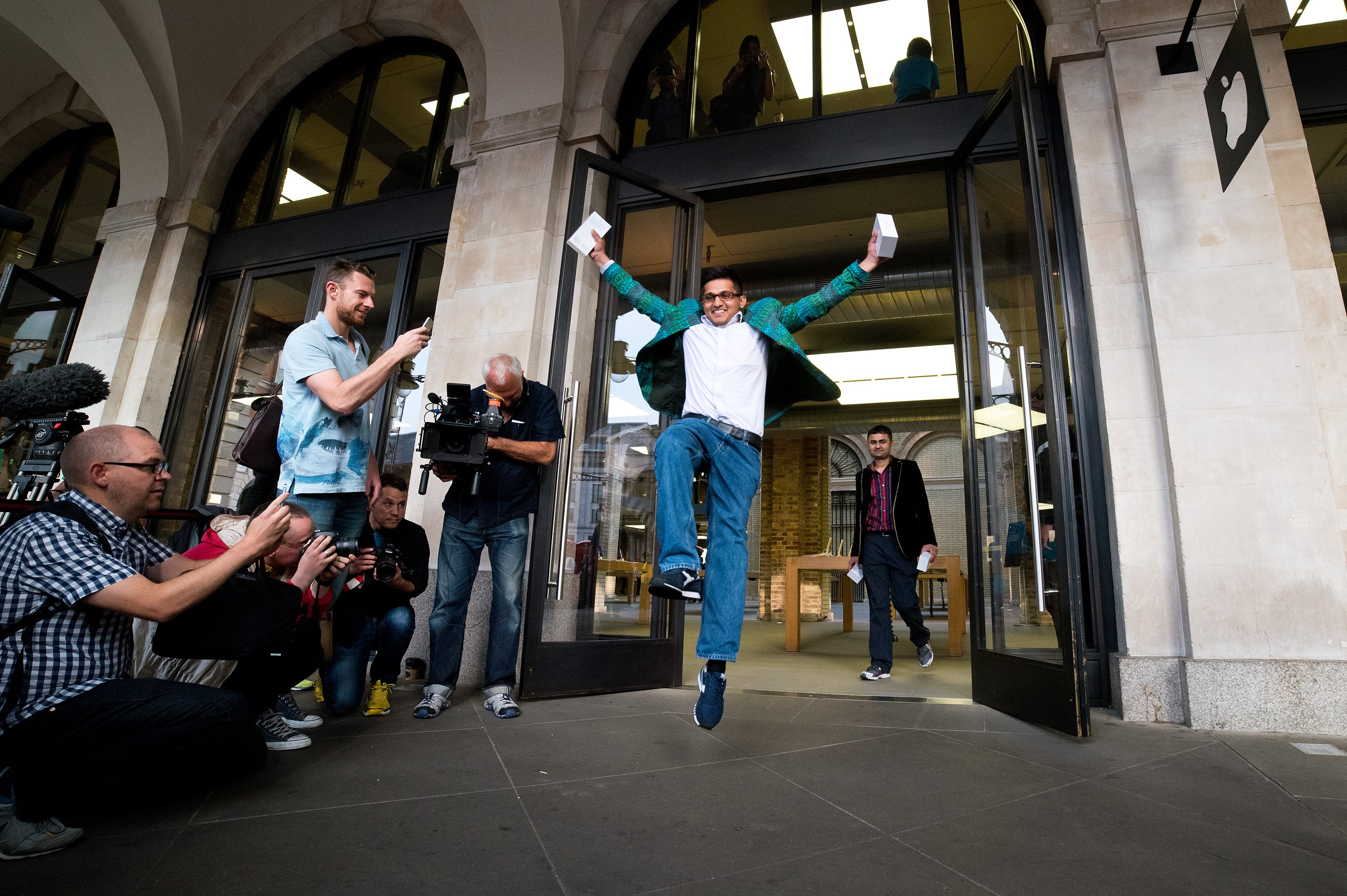 Jamael Ahmed jumps in the air as he leaves the store after being the first to purchase the iPhone 6 at Apple Covent Gardens  in London on Sept. 19, 2014.