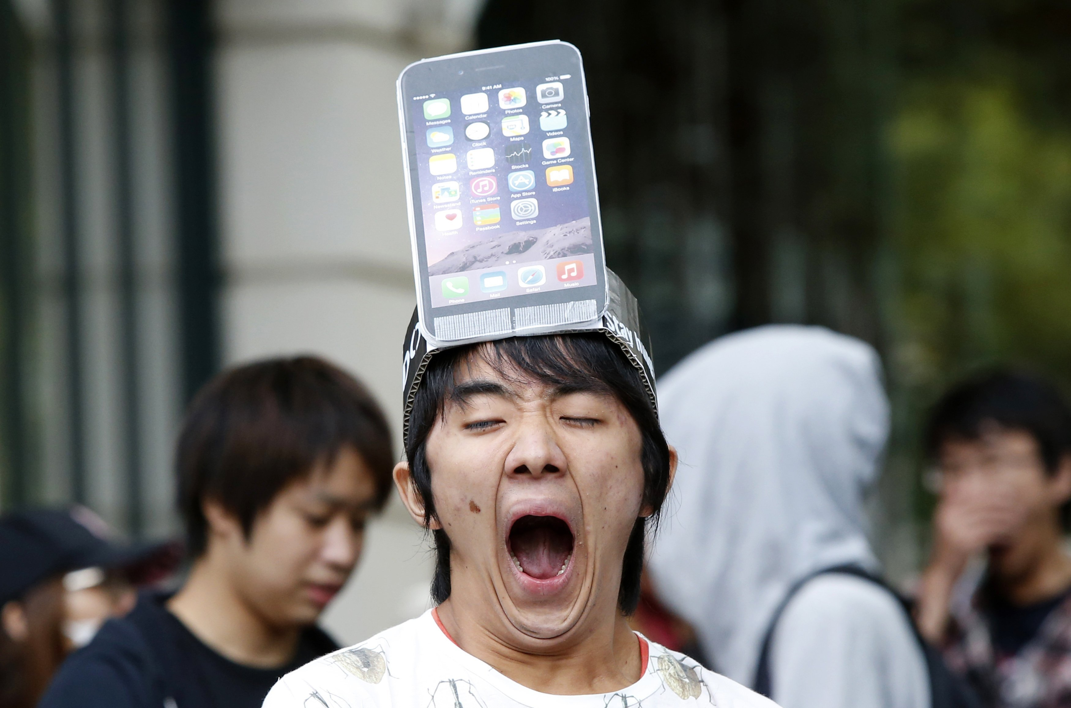 A man wearing a replica of an iPhone 6 Plus model on his head yawns while waiting in front of an Apple Store in Tokyo on Sept. 19, 2014.