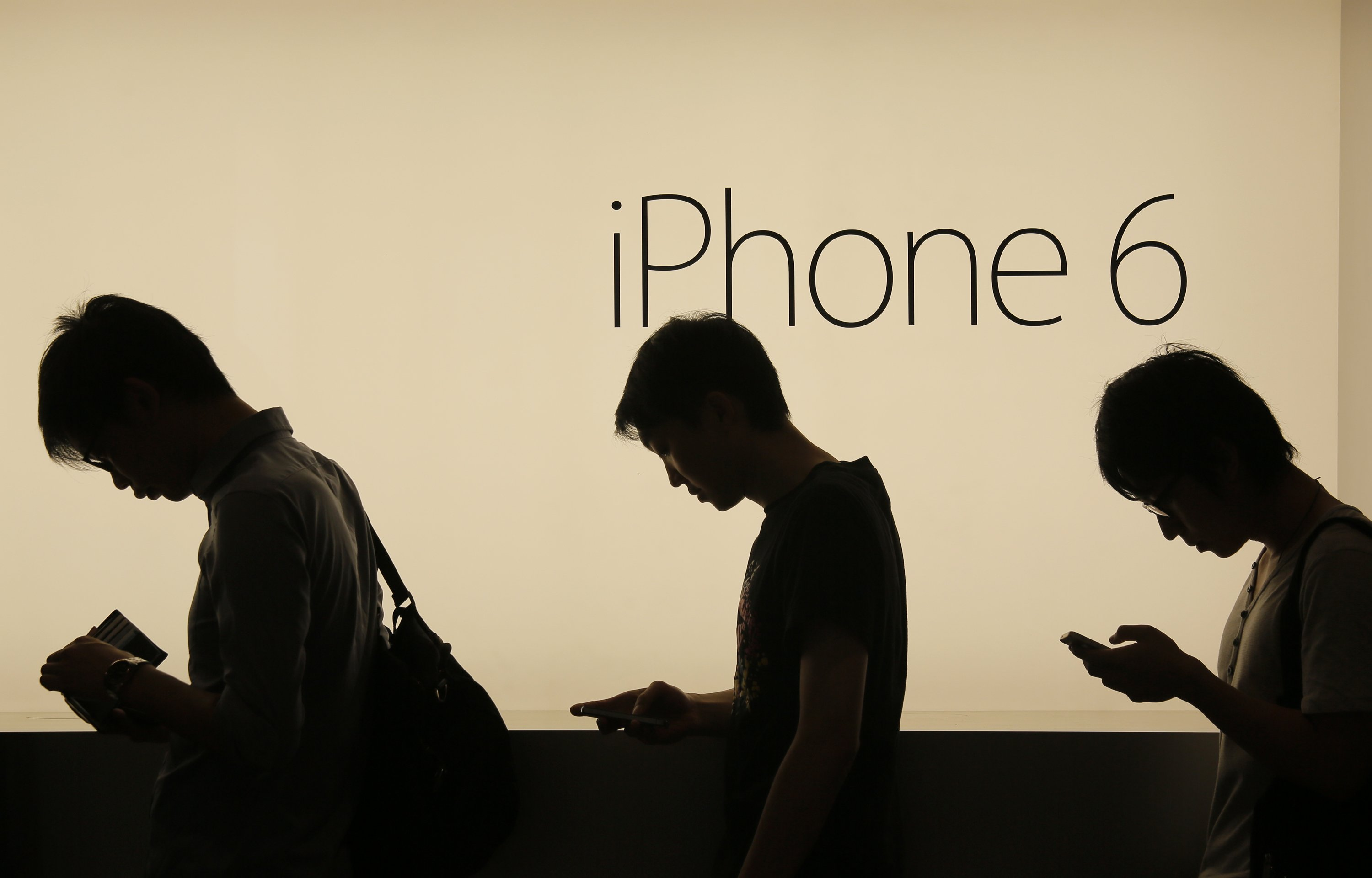 People wait to buy the new Apple iPhone 6 and 6 Plus devices outside an Apple store in Hong Kong on Sept. 19, 2014