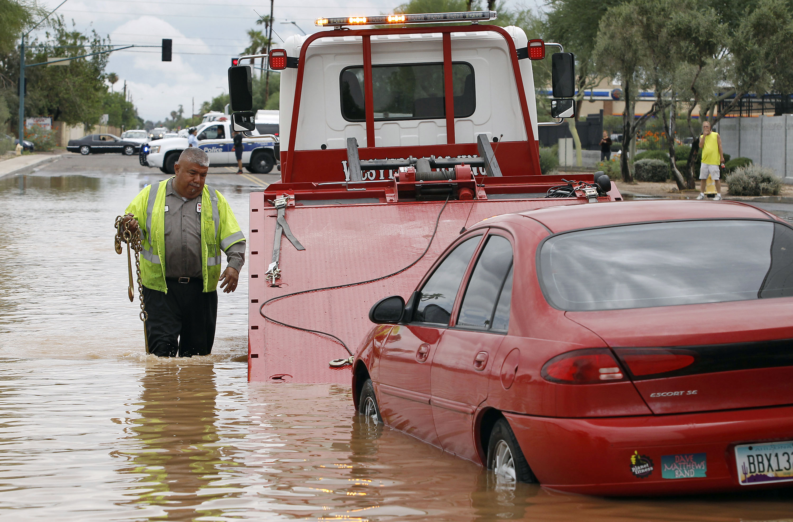 Steven Martinez of Western Towing prepares to lift a vehicle stranded in about 2 ft. of water in Phoenix on Sept. 8, 2014