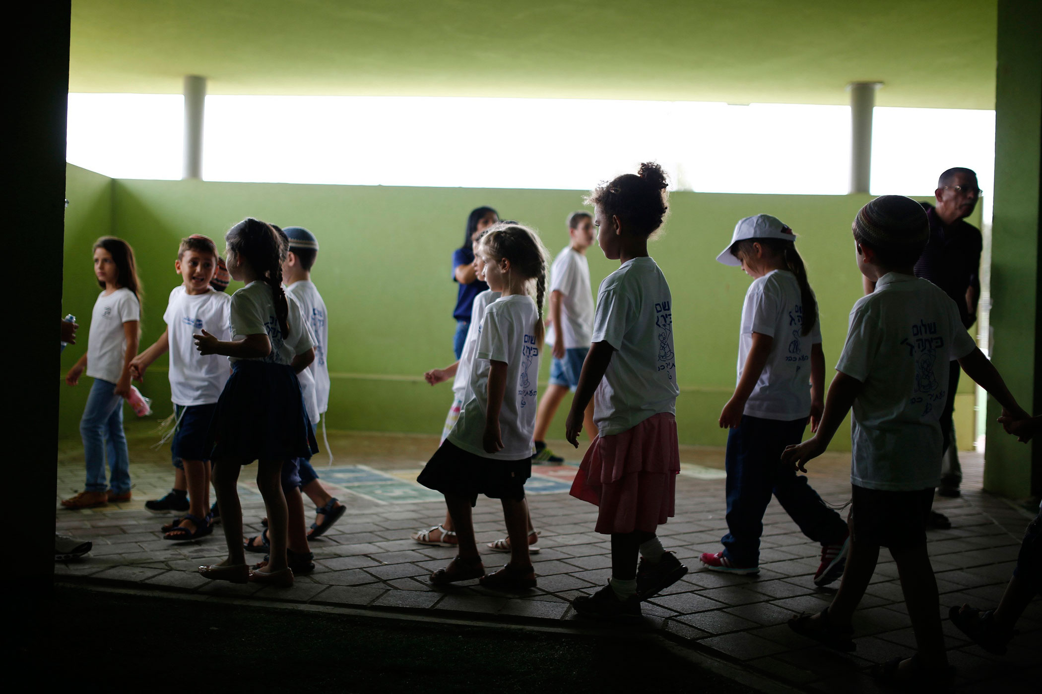Israeli children walk in a school which is reinforced against rocket and mortar attacks, on the first day of the school year in Kibbutz Saad, outside the Gaza Strip on Sept. 1, 2014.