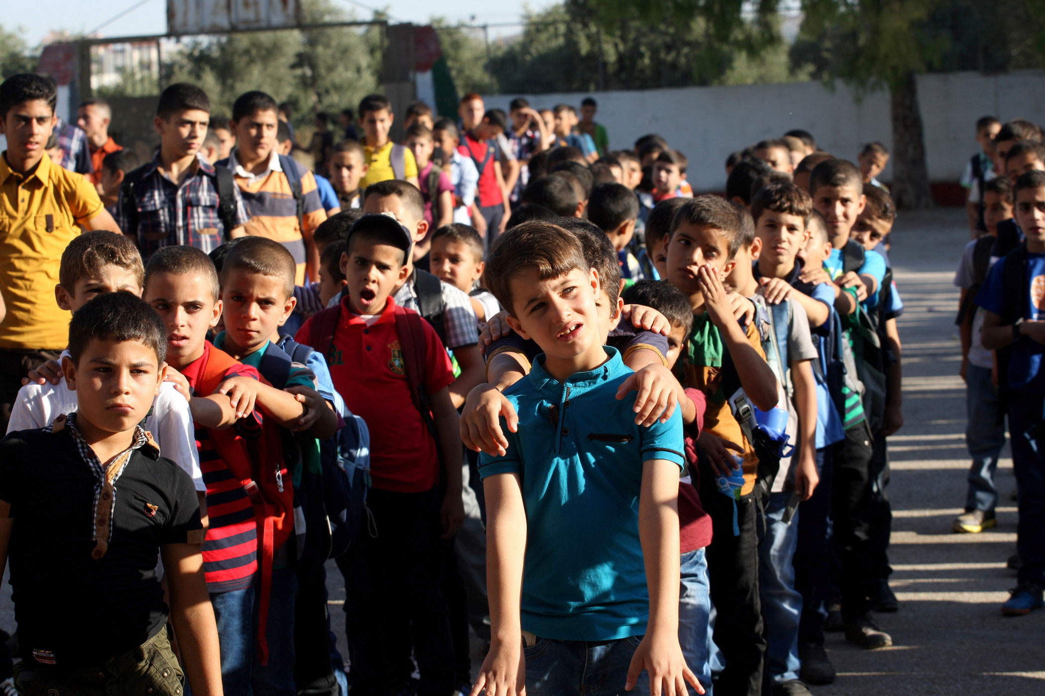 Palestinian students return back to their school in the morning of the first day of the new school year in the West Bank city of Nablus, on Aug. 24, 2014