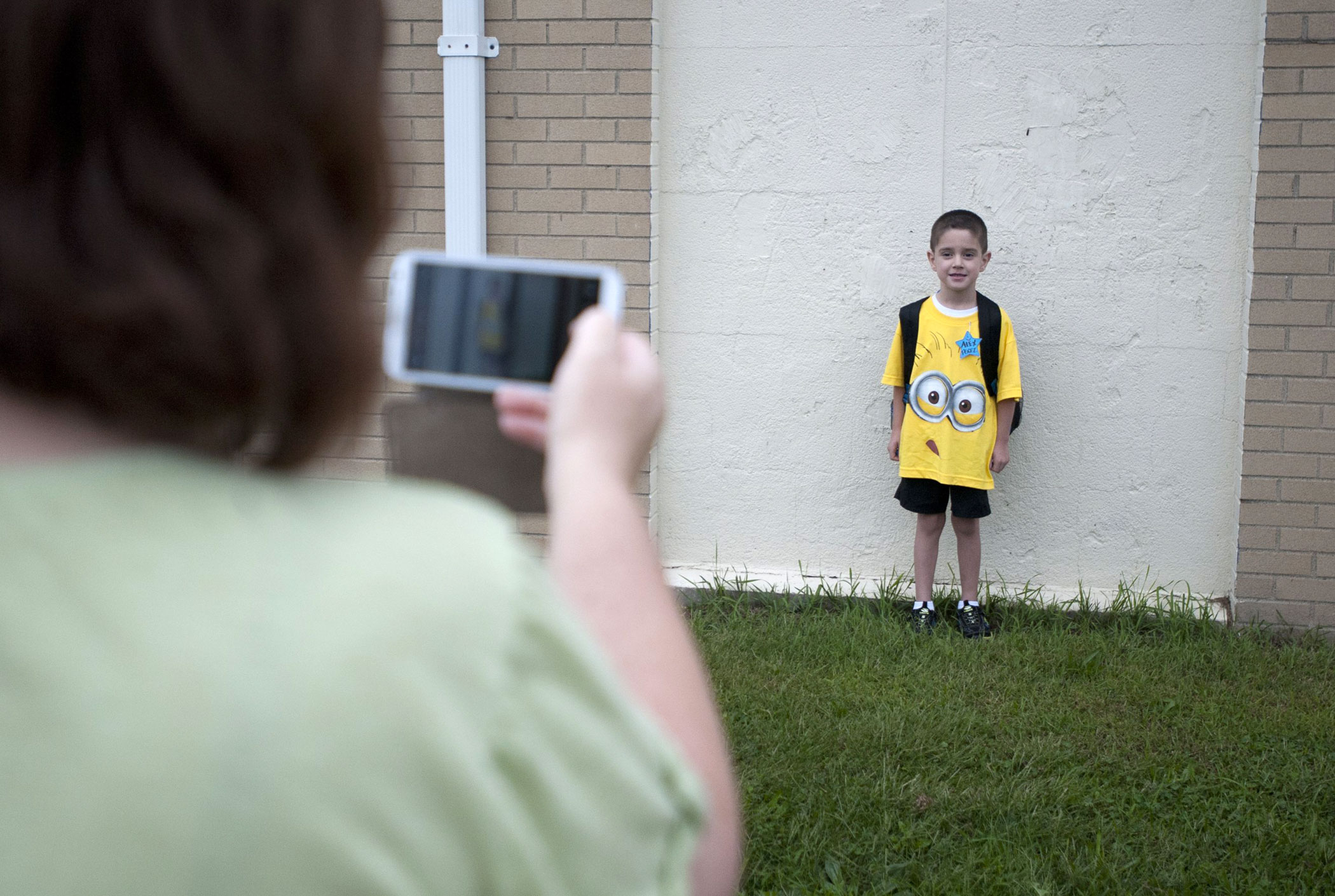 Alex Perez, 5, has his picture taken before the first day of school by Kelly Cunningham at Northwest's Parnall Elementary School on Sept. 2, 2014 in Jackson, MI.