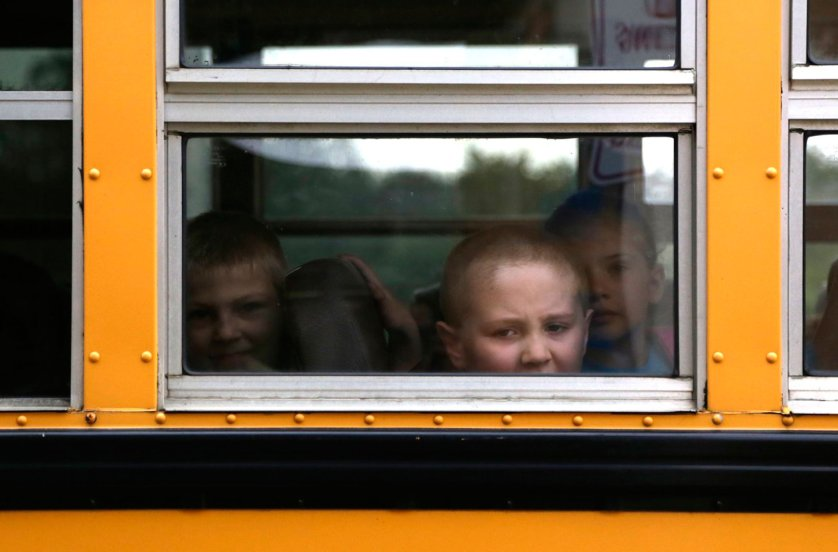 A student looks out of a bus toward Bertha Robinson Elementary school during the first day back from summer break on Sept. 2, 2014 in Leoni Township, MI.