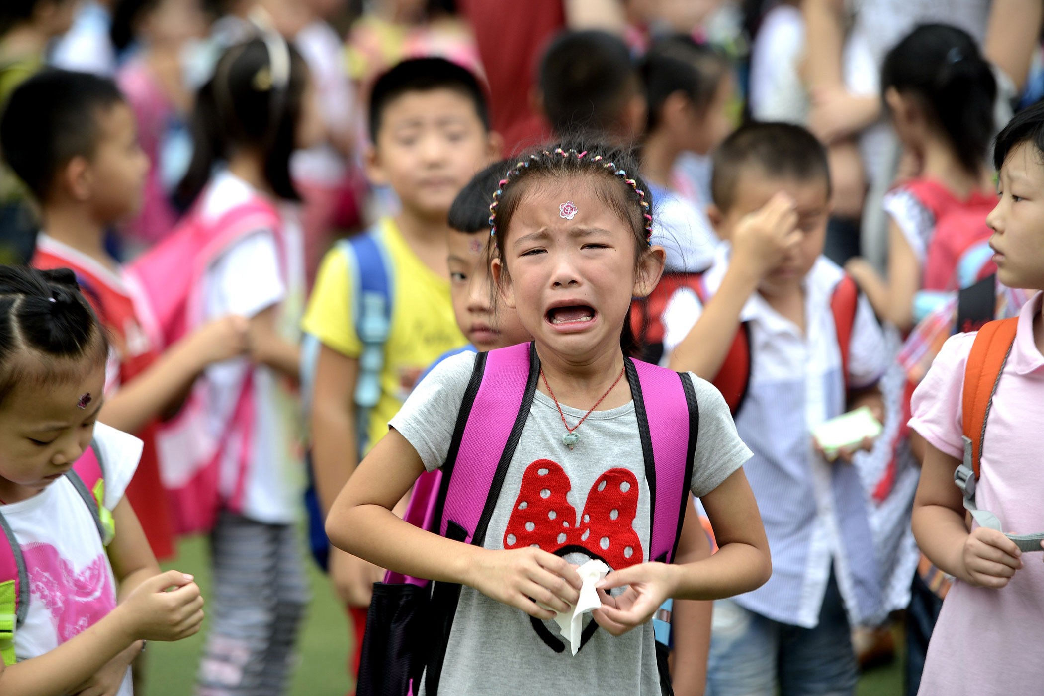 Elementary school students enter school with their parents on Sept. 1, 2014 in Jinan, Shandong province of China. Monday is the first day of school in 2014.