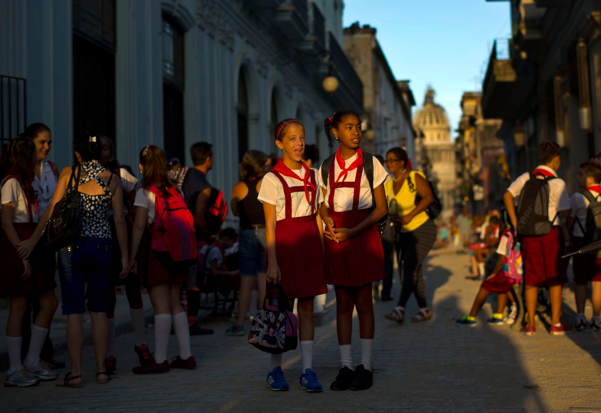 Girls in their uniforms wait for a classmate before going to school in Old Havana, Cuba on Sept. 1, 2014. Monday marked the first day back to class for students across Cuba.
