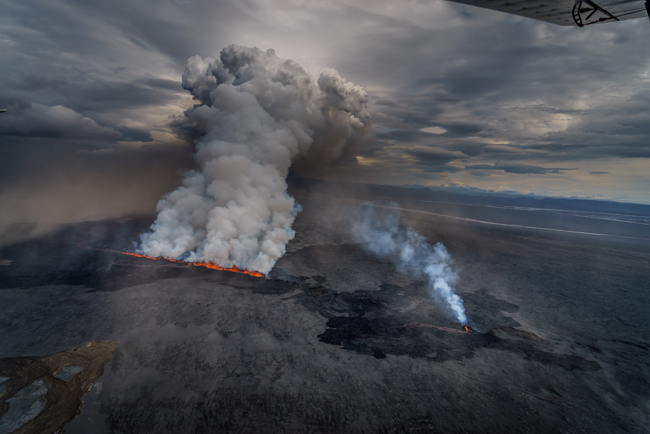 Heavy activity in the northern half of the fissure sent a white plumb some 15,000 feet into the sky and pushed lava across the cold sand below. Bardarbunga, Sept. 1.