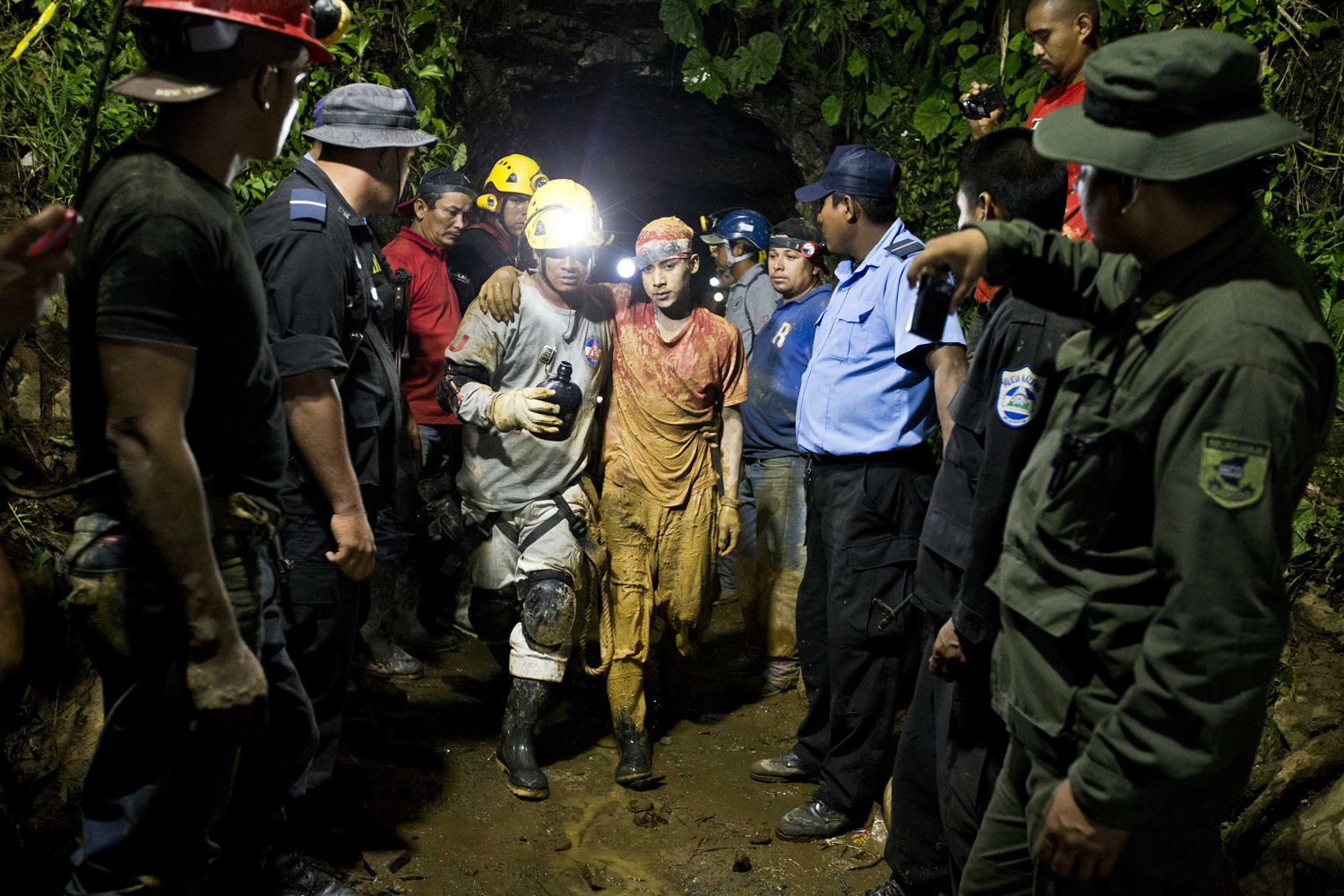 Aug. 29, 2014. Leber Vivas Gonzales, 16, center right, is accompanied by a rescue worker as he walks away from the entrance to the El Comal gold and silver mine in Bonanza, Nicaragua. Vivas was the first of 11 freelance gold miners trapped by a collapse in the mine to be rescued and crews were working early Saturday to free more the rest, officials said.
