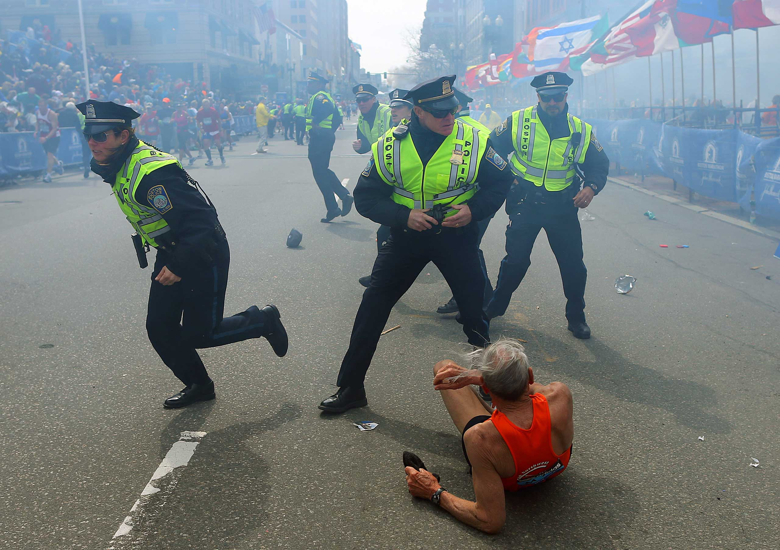 April 15, 2013. Boston police officers react to a second explosion near the finish line of the 117th Boston Marathon.