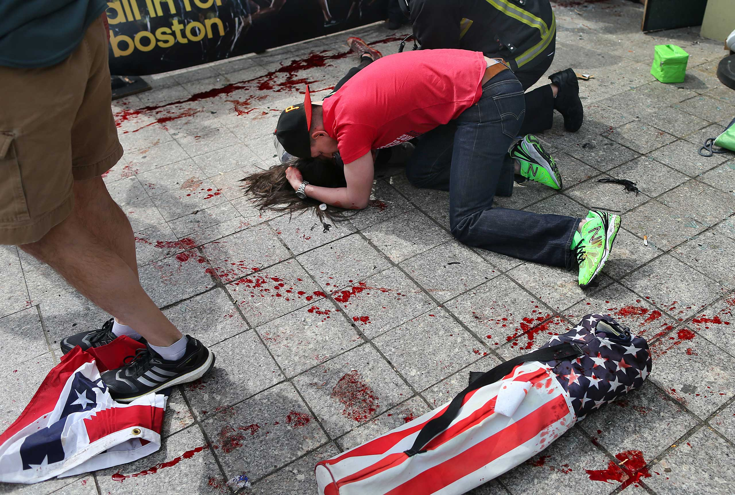 April 15, 2013. A man comforts a victim on the sidewalk at the scene of the explosion.