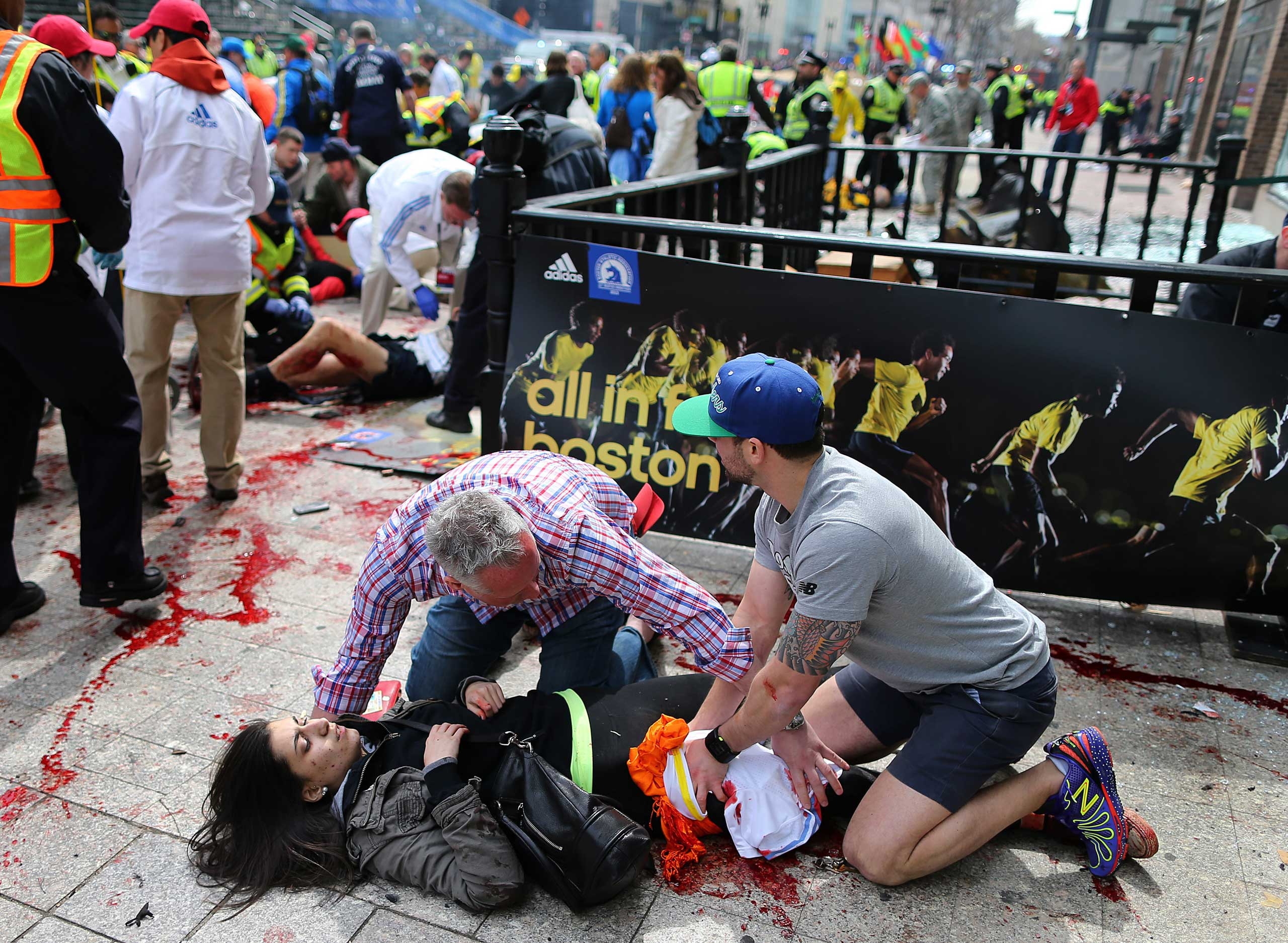 April 15, 2013. Bystanders help a wounded woman at the scene of the first explosion on Boylston Street near the finish line.