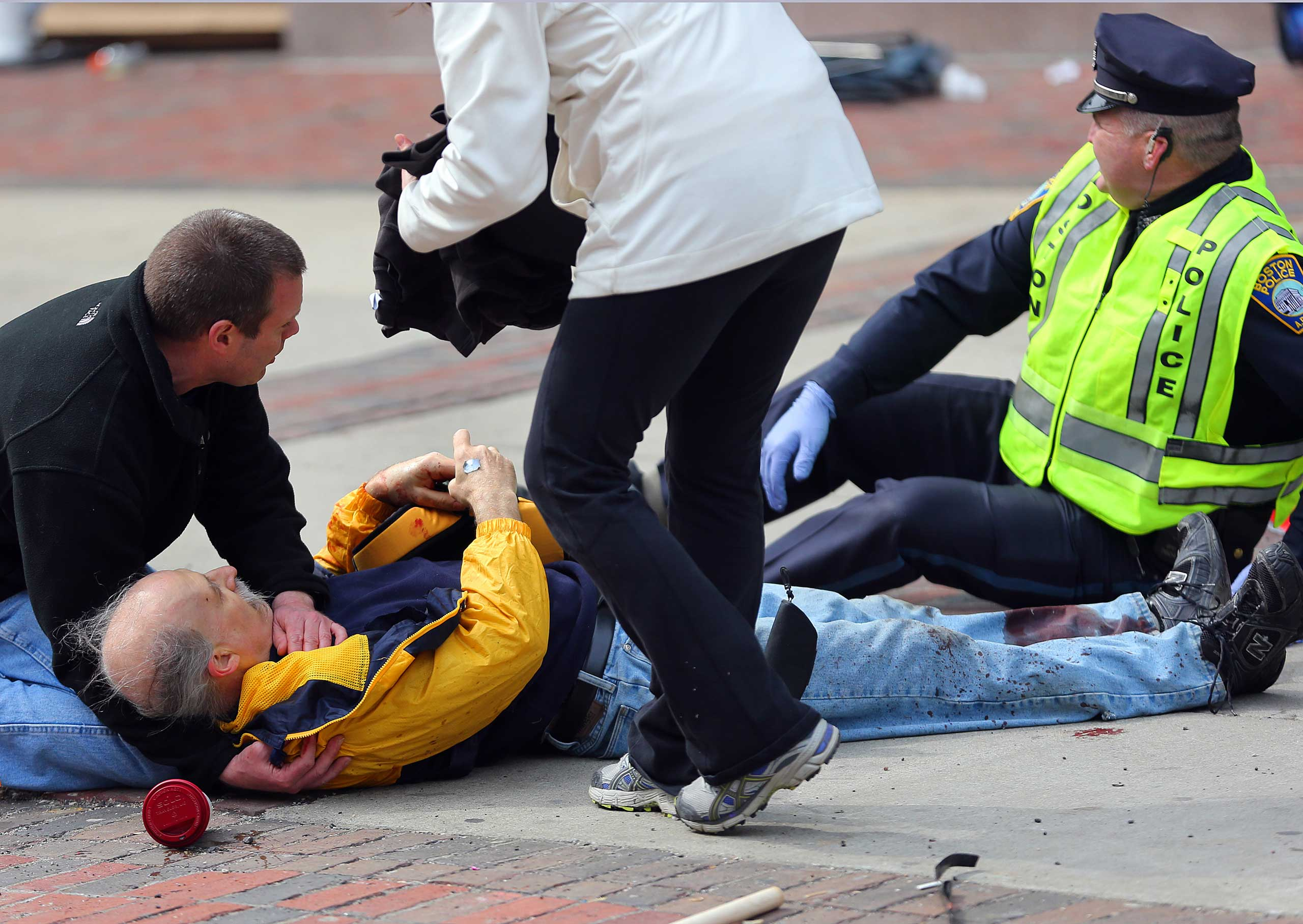 April 15, 2013. A wounded man is helped on the sidewalk at the scene of the first explosion.