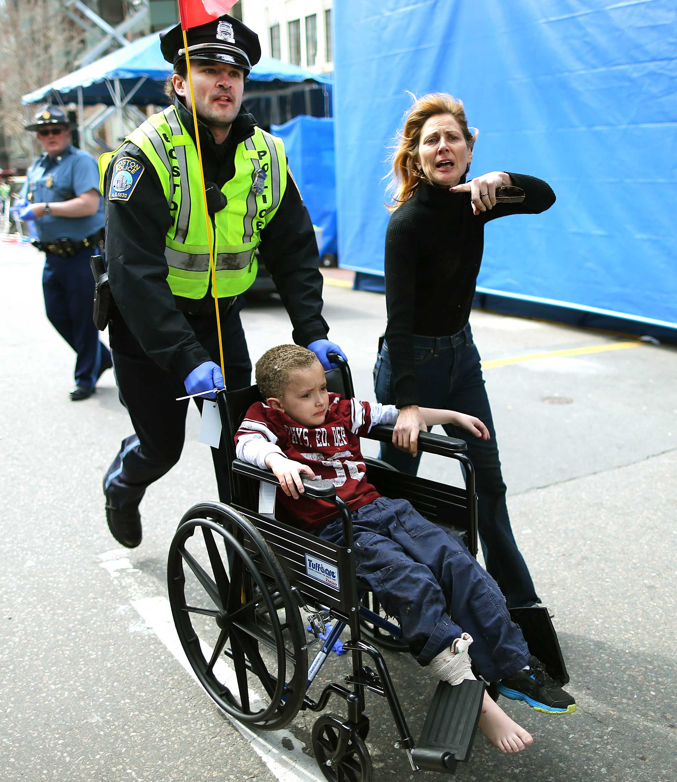 April 15, 2013. A wounded boy is evacuated from the scene by a Boston police officer.