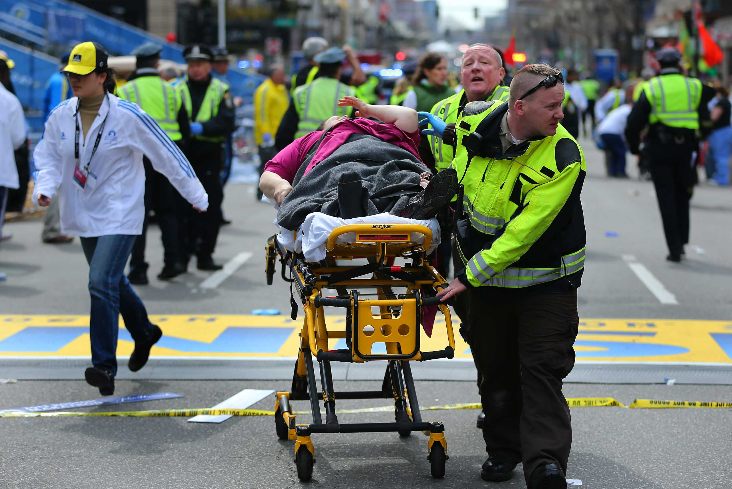 April 15, 2013. A victim from the explosion is wheeled away from the scene by emergency personnel.