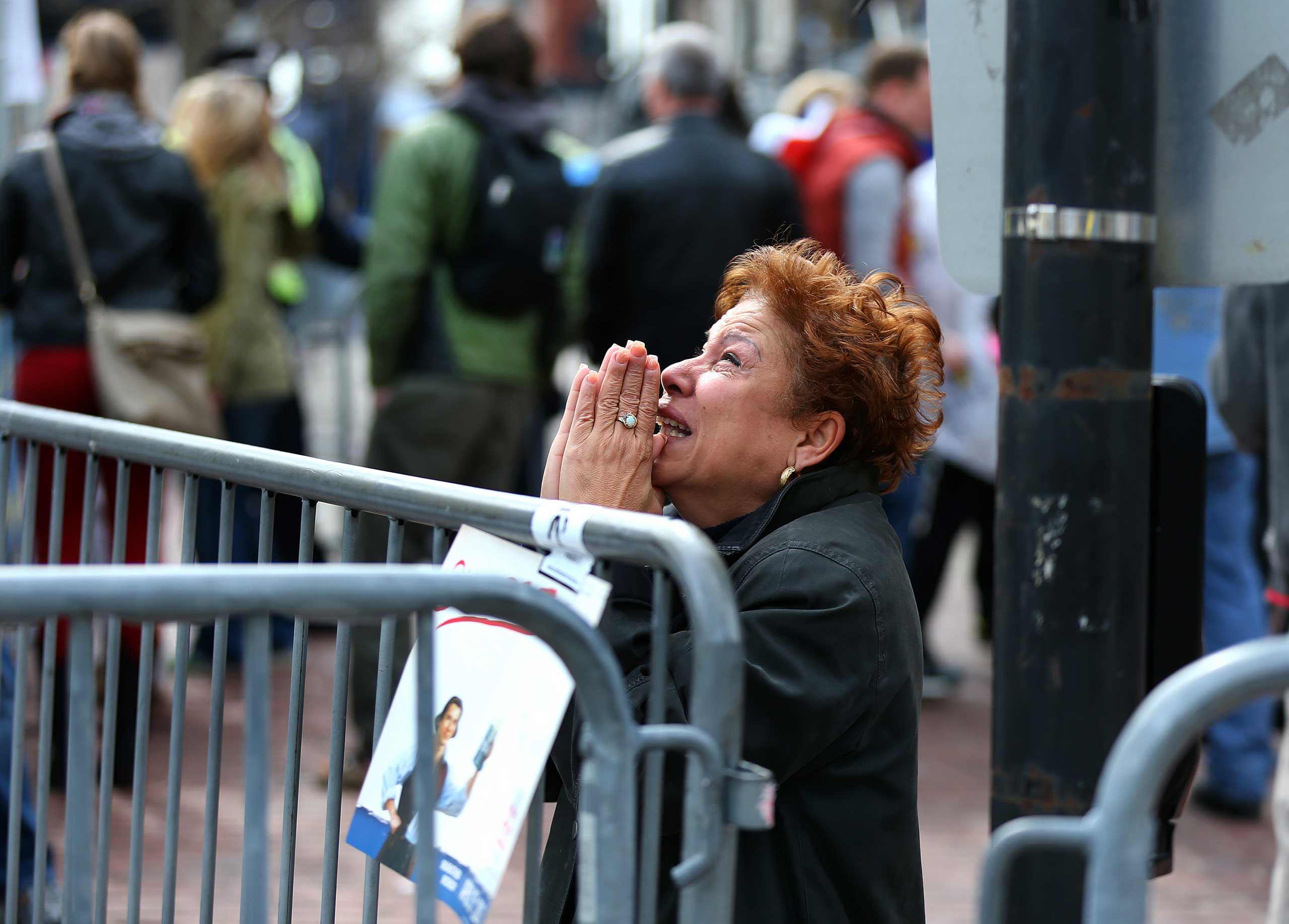 April 15, 2013. A woman prays at the scene of the explosion.